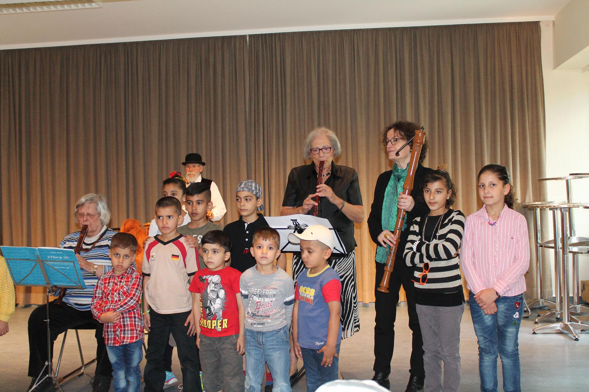 Flötenkreismitglieder, Kinder aus der Erstaufnahmeeinrichtung, Drehorgelspieler im Hintergrund