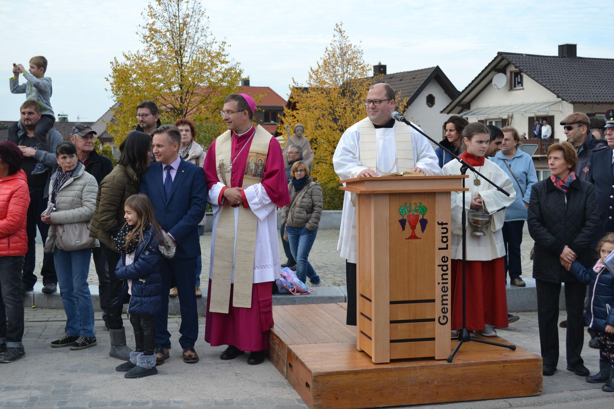Allocution du curé, à côté de lui le Maire et l'Evêque, en arrière-plan la statue de  St. Leonhard sur la place de la Mairie