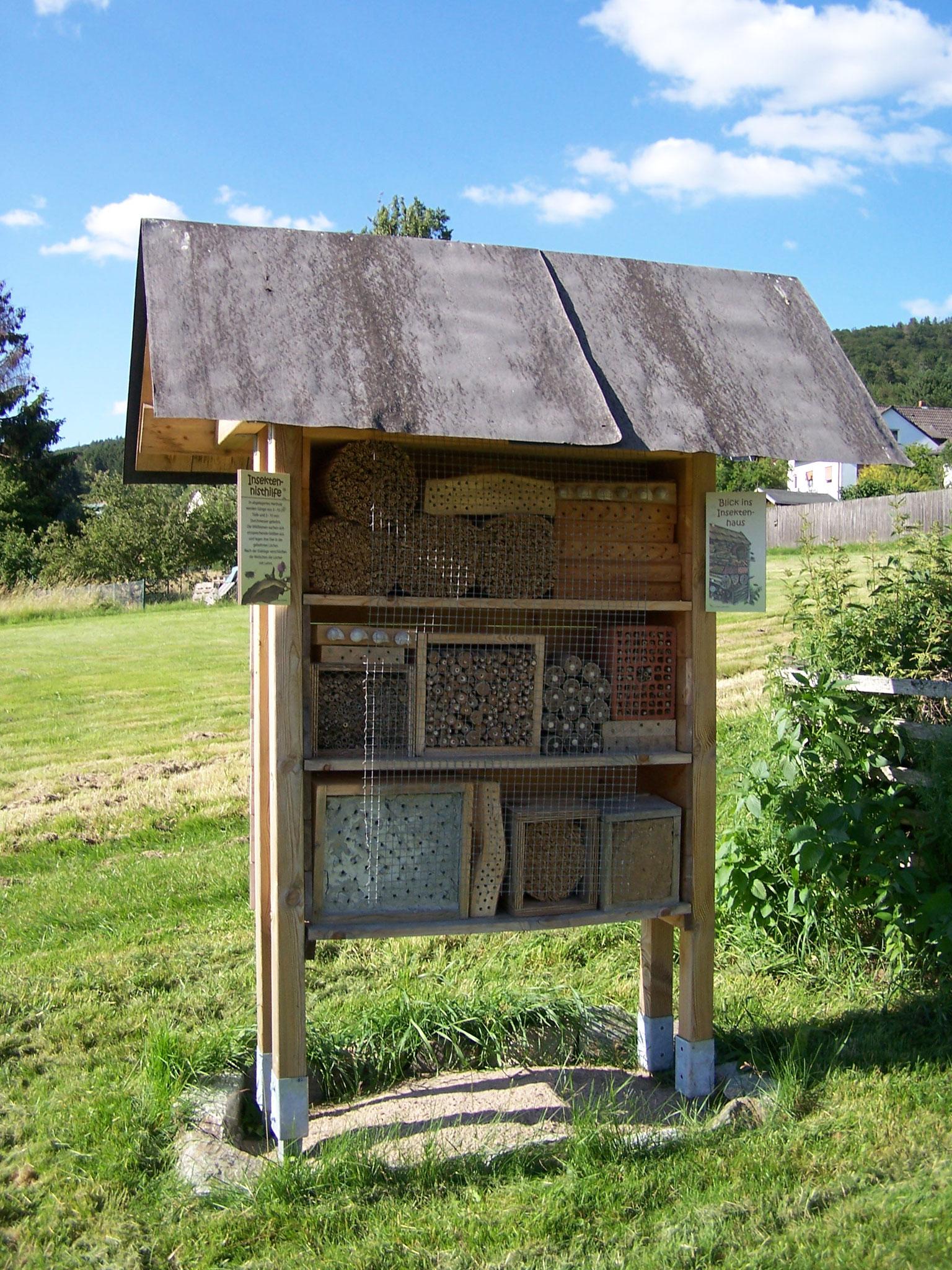 das Insektenhotel mit kleinen Informationstafeln und Flyerboxen auf der Rückseite