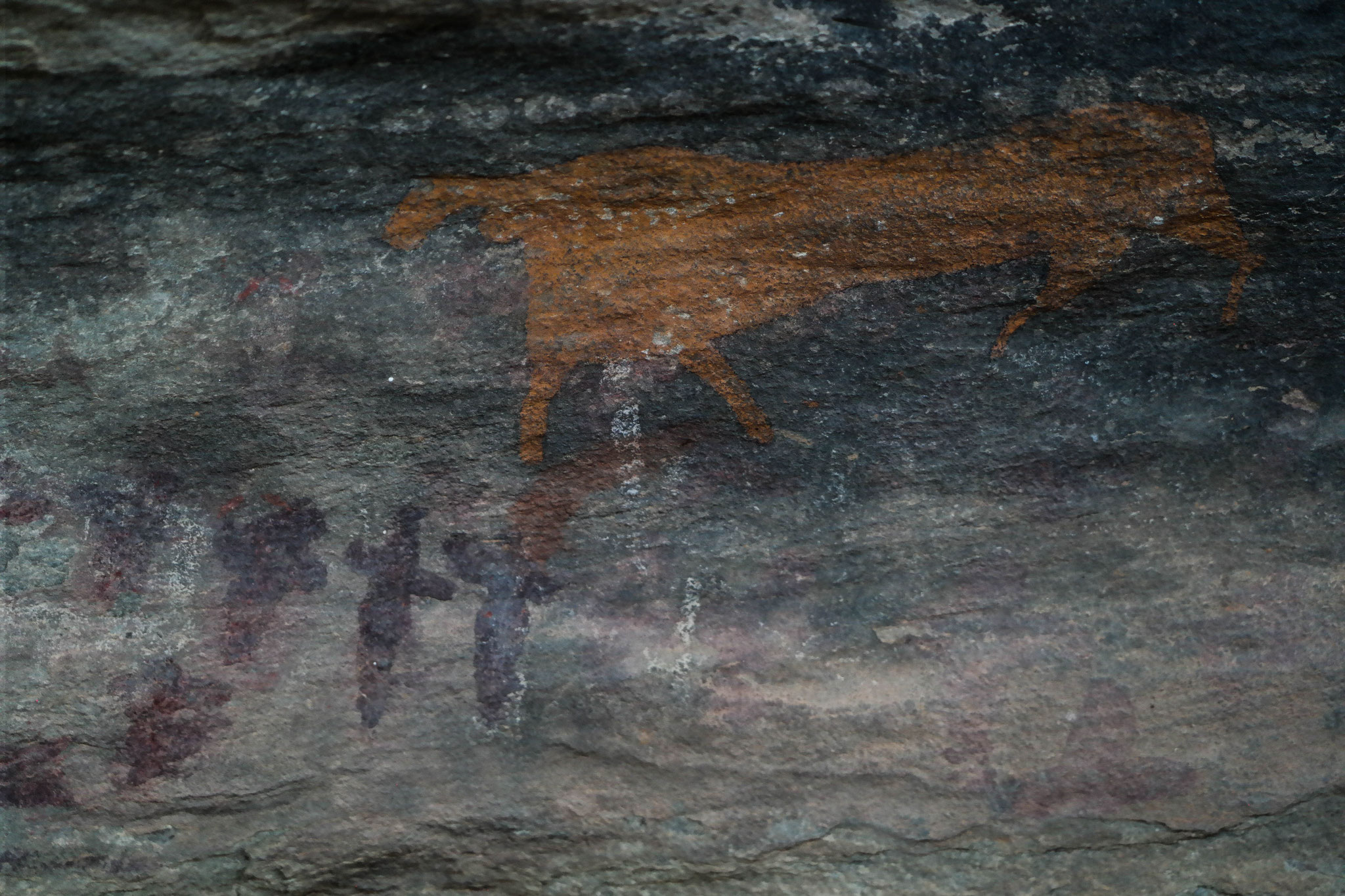 A brown animal painting with people in the bottom left.