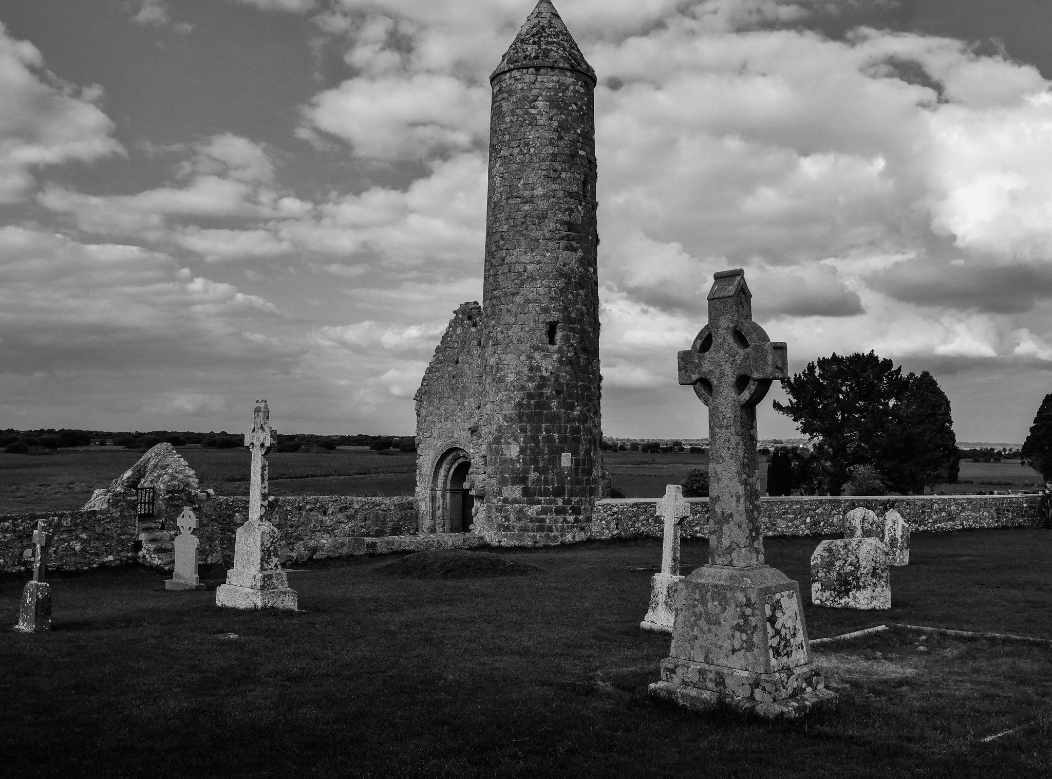 """Samhain"": black and white shot of an old tower at the edge of an anvient graveyard."