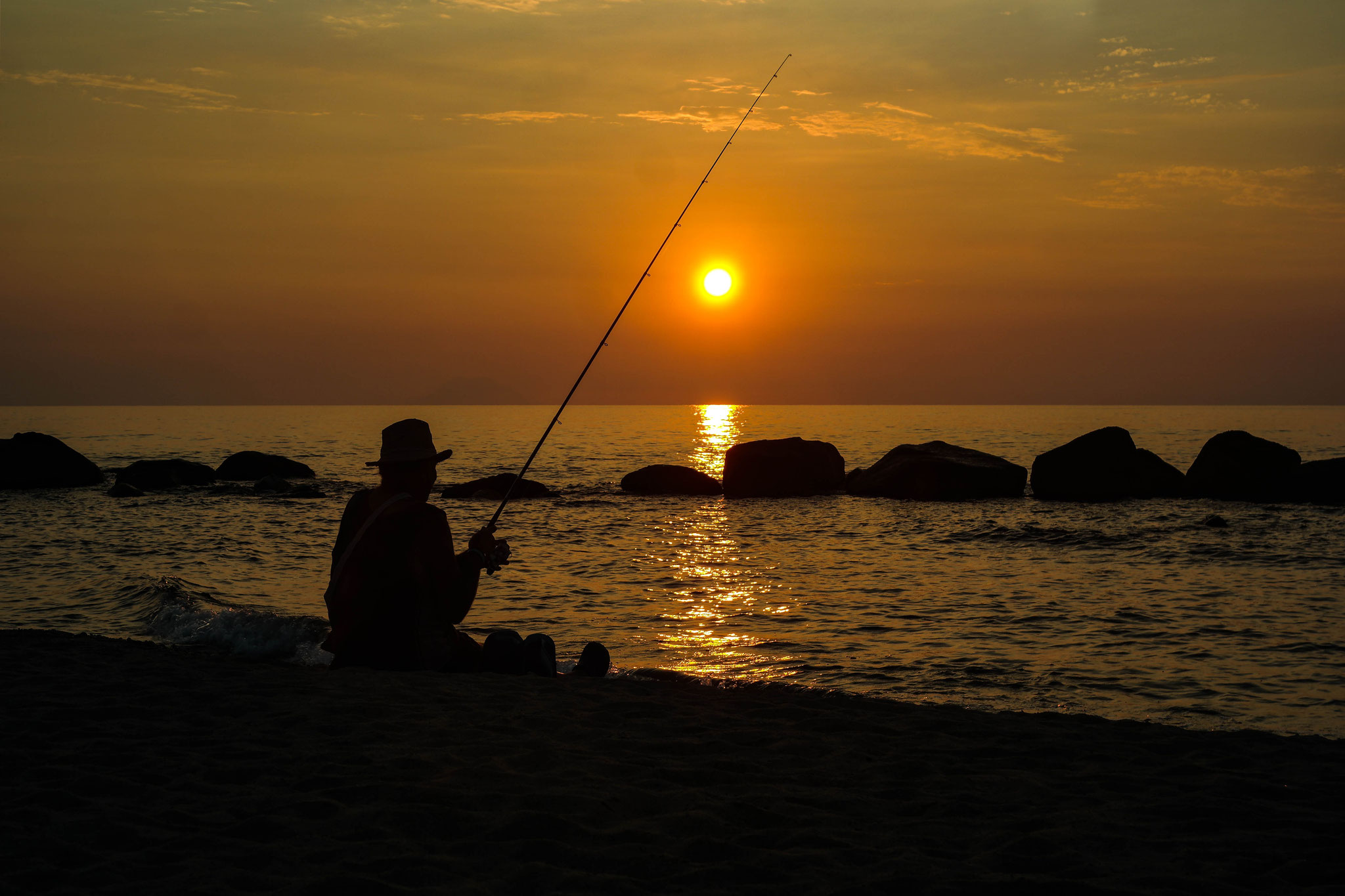 Fisherman sitting on the beach in front of the sea and the sunset