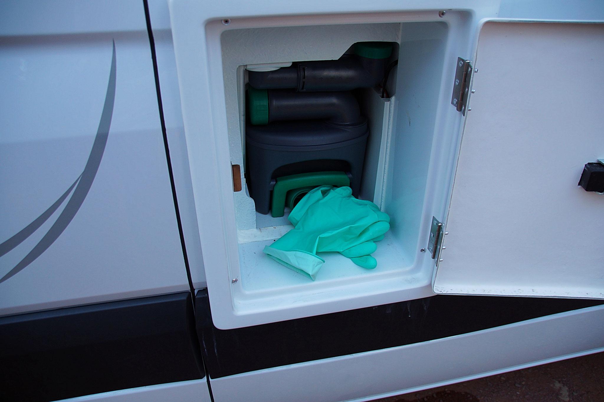 Klo-Abwassertank mit Handschuhen