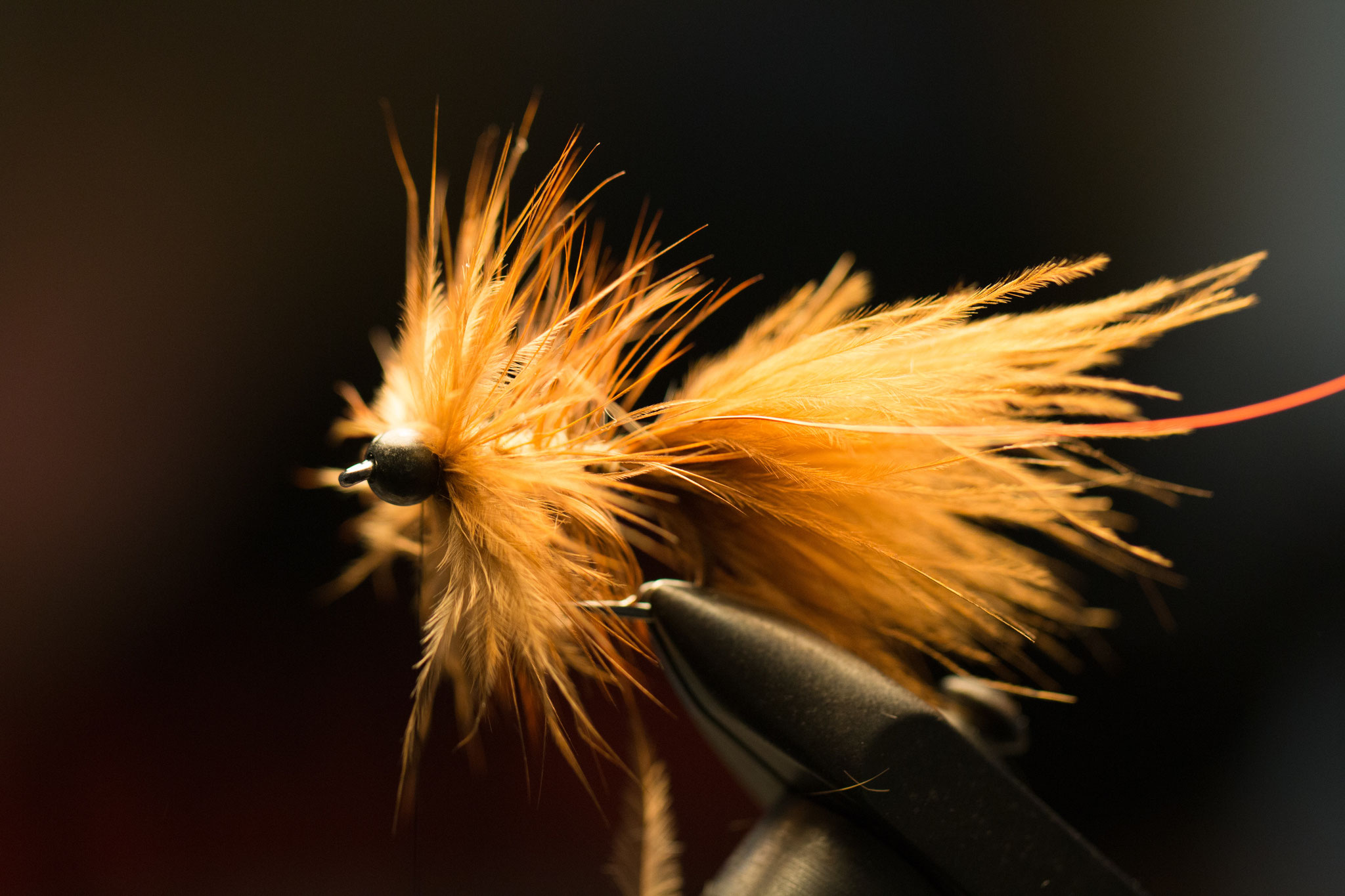 After dubbing the hook (you can use dubbing brushes, makes it very easy), wind the saddle hackle towards the bead. Make a couple of turns directly behind the bead to make kind of a head.