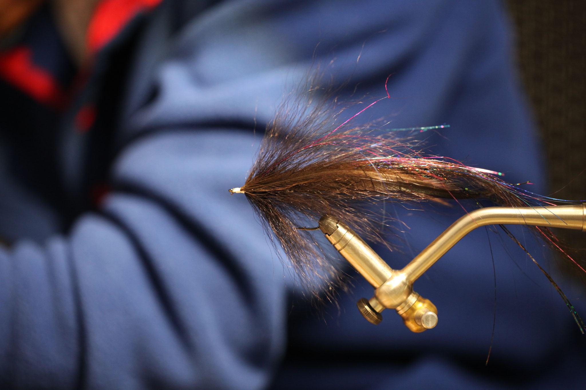 Build a collar with reverse tied bucktail, add more flash and feathers and finish with another collar, then whip finish