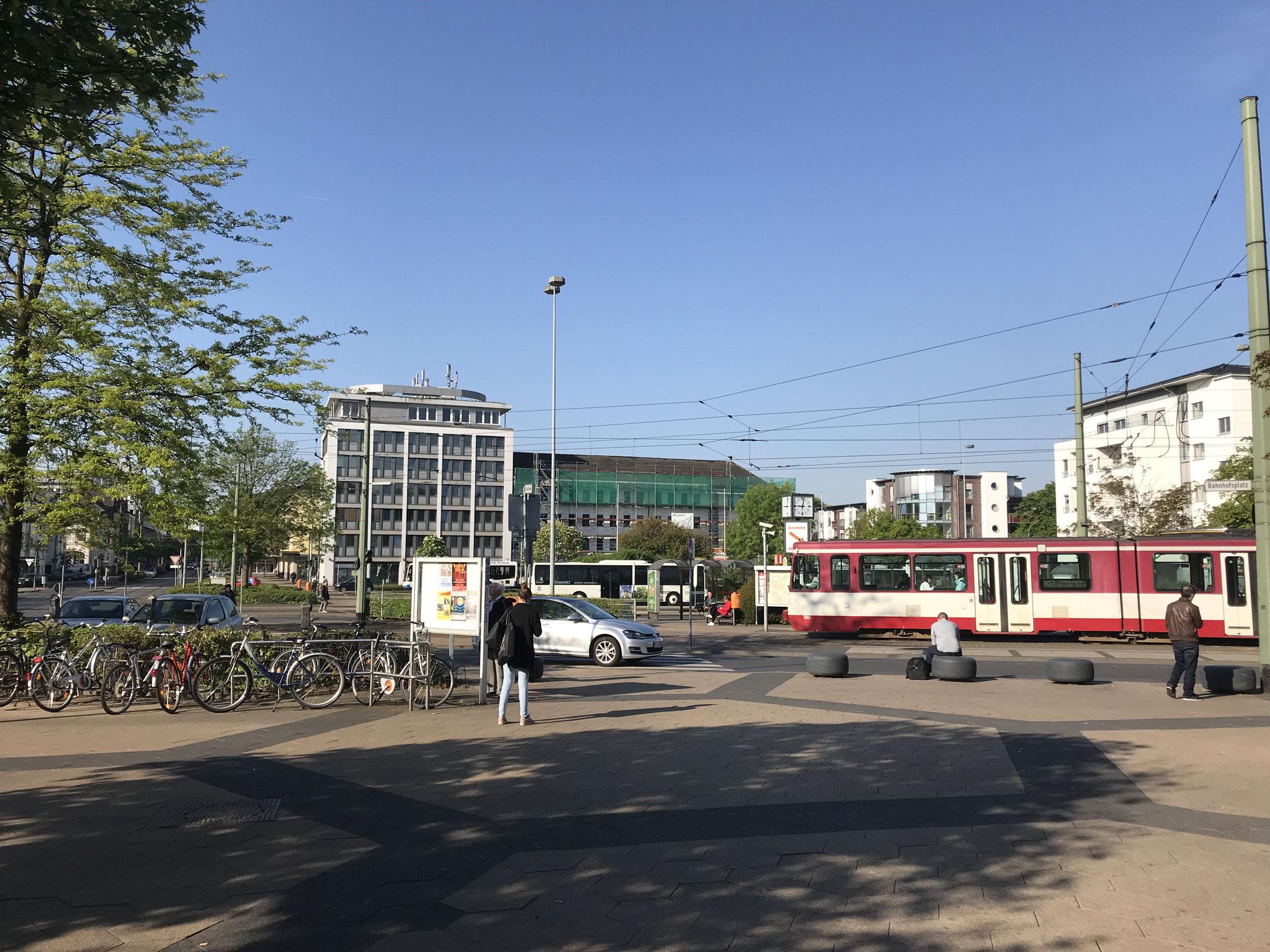 Haltende Straßenbahn vor dem Bahnhofsgebäude.