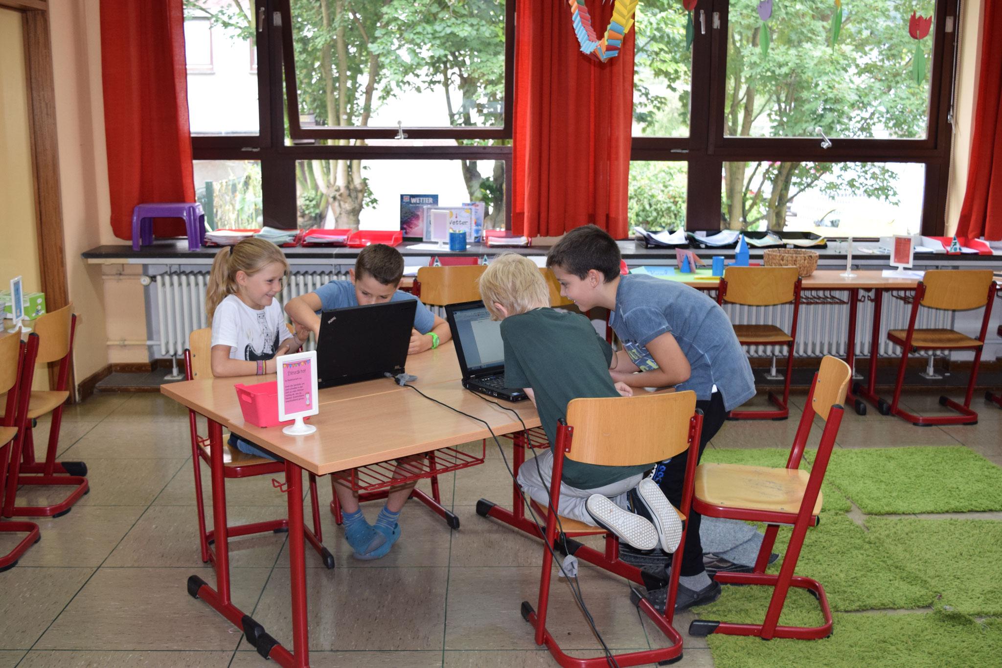 Die Kinder arbeiten an den Laptops.