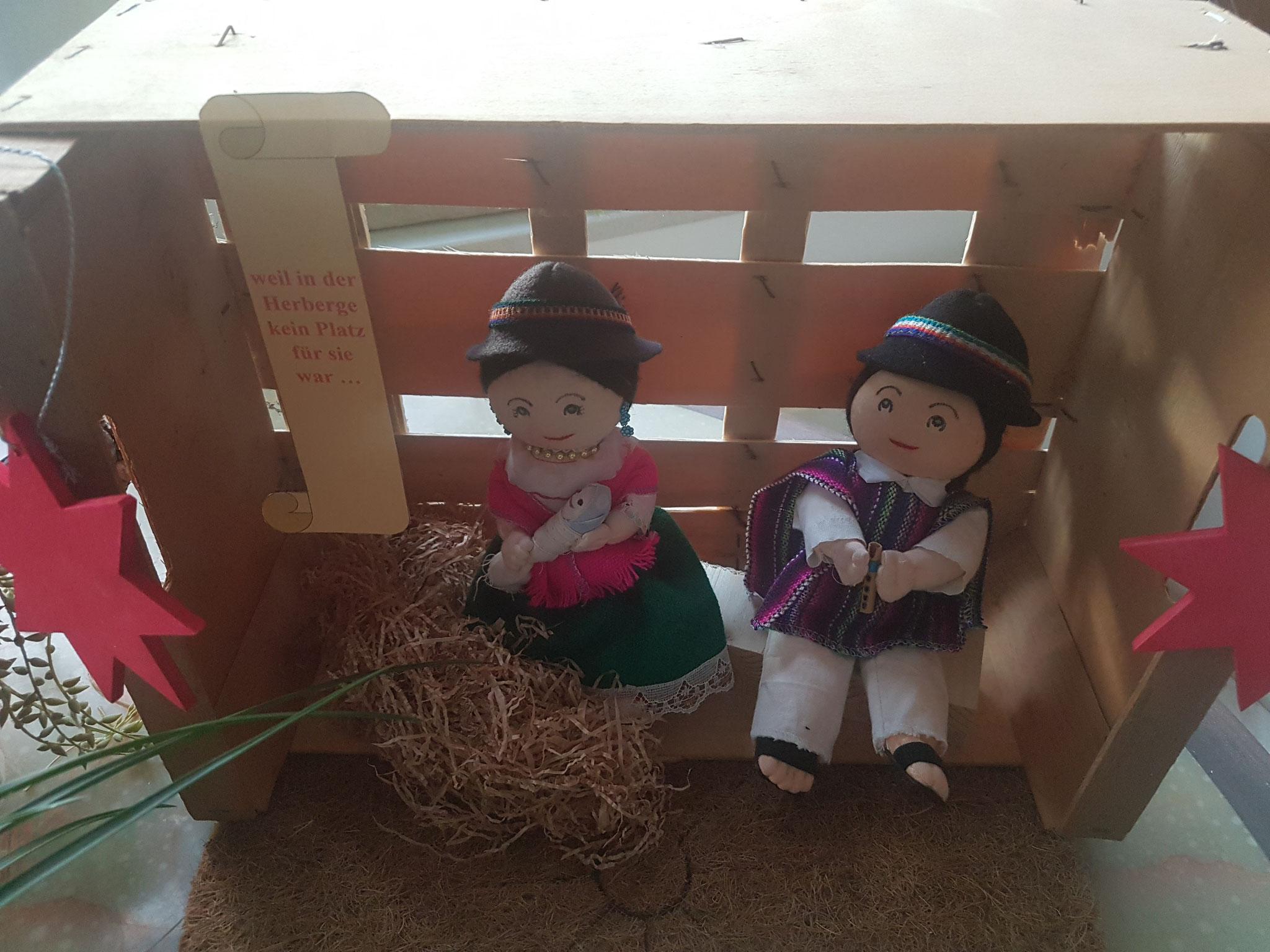 """Benno Jacobi. Die Figuren stammen aus Ecuador und stehen in der Tradition der indigenen Bevölkerung Südamerikas. Zusammen mit der Obstkiste als """"Stall"""" stehen sie in besonderer Weise für all die Menschen, die unbehaust Weihnachten begehen müssen."""