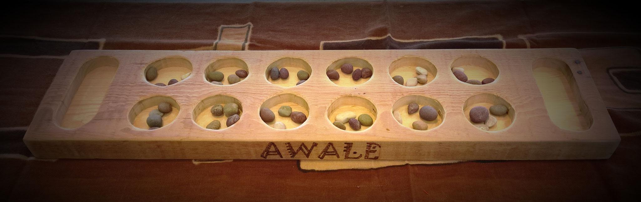 l'Awalé de la famille des mancalas, l'un des jeux le plus répandu en Afrique et ayant le plus voyagé avec les migrations des peuples