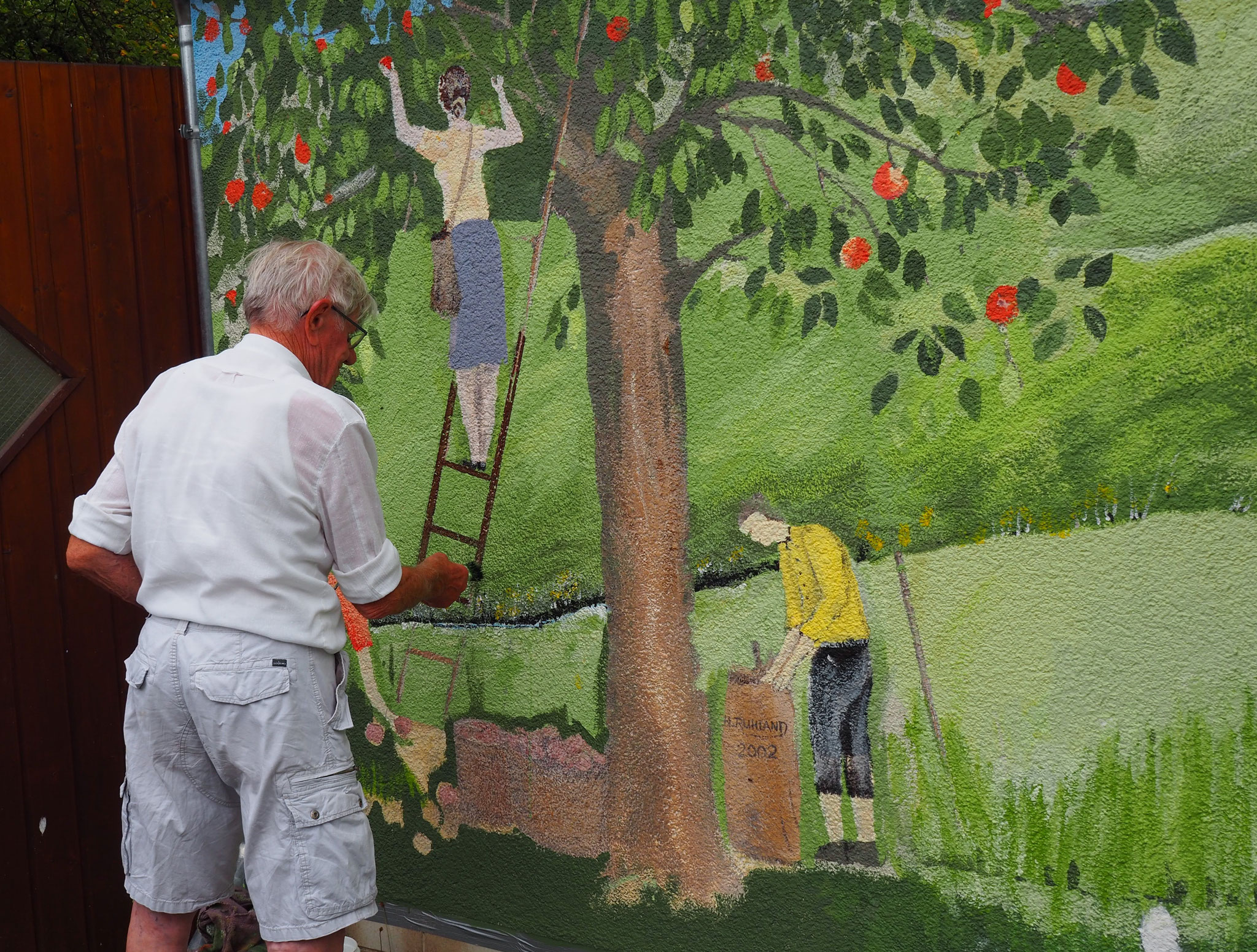 Malermeister Fritz Roos beim Restaurieren des Wandbilds.