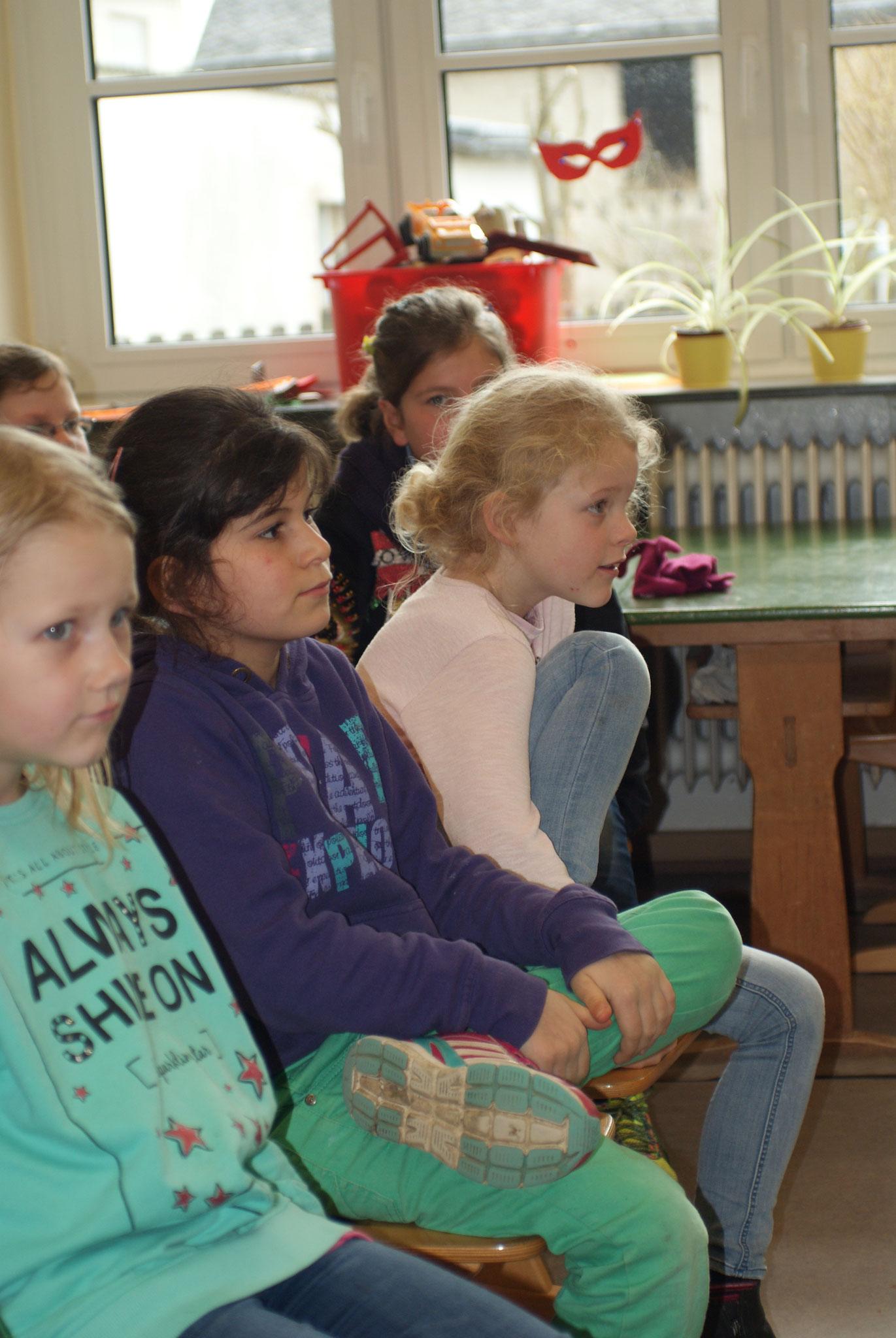 Die Mädchen des 1. Schuljahres hören gespannt zu.