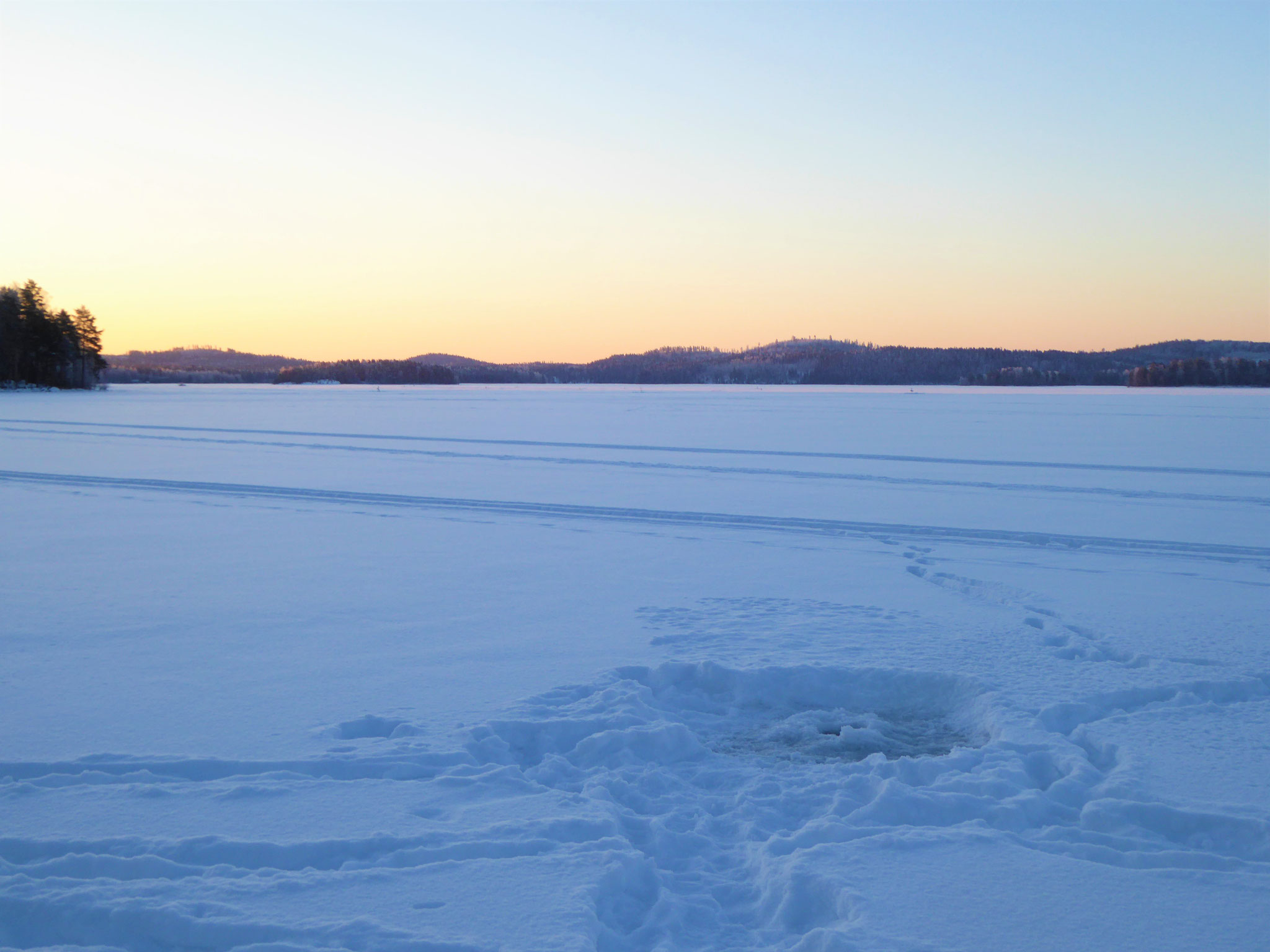 Ice fishing on the lake in front of log house and ...