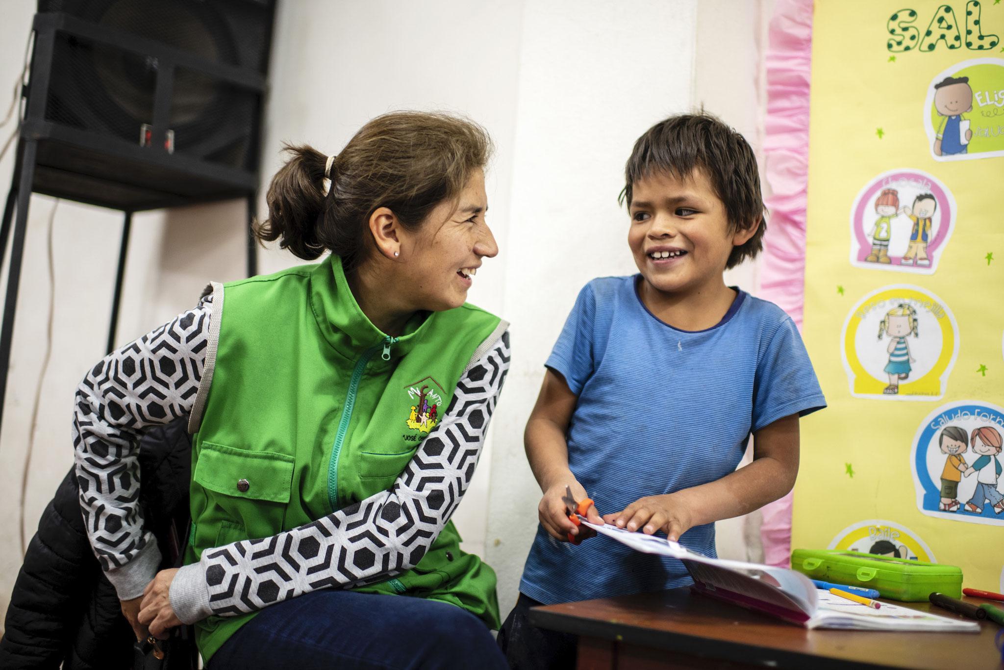 Projektleiterin Dianira Trigoso Vizconde hilft dem 8-jährigen Moises bei den Hausaufgaben. Foto: Florian Kopp / Kindermissionswerk