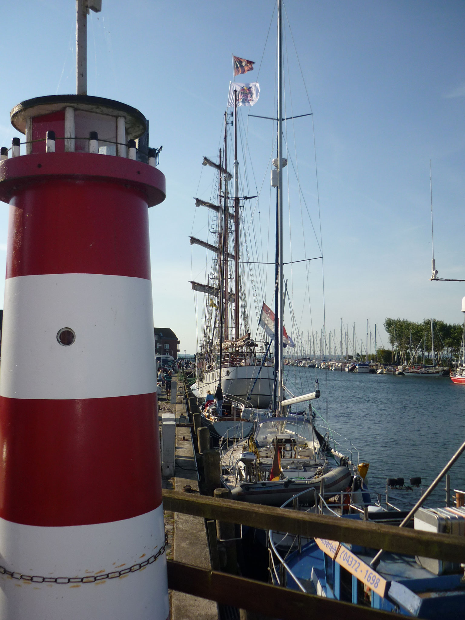 Leuchtturm und riesige Segelyacht, Hafen Orth auf Fehmarn