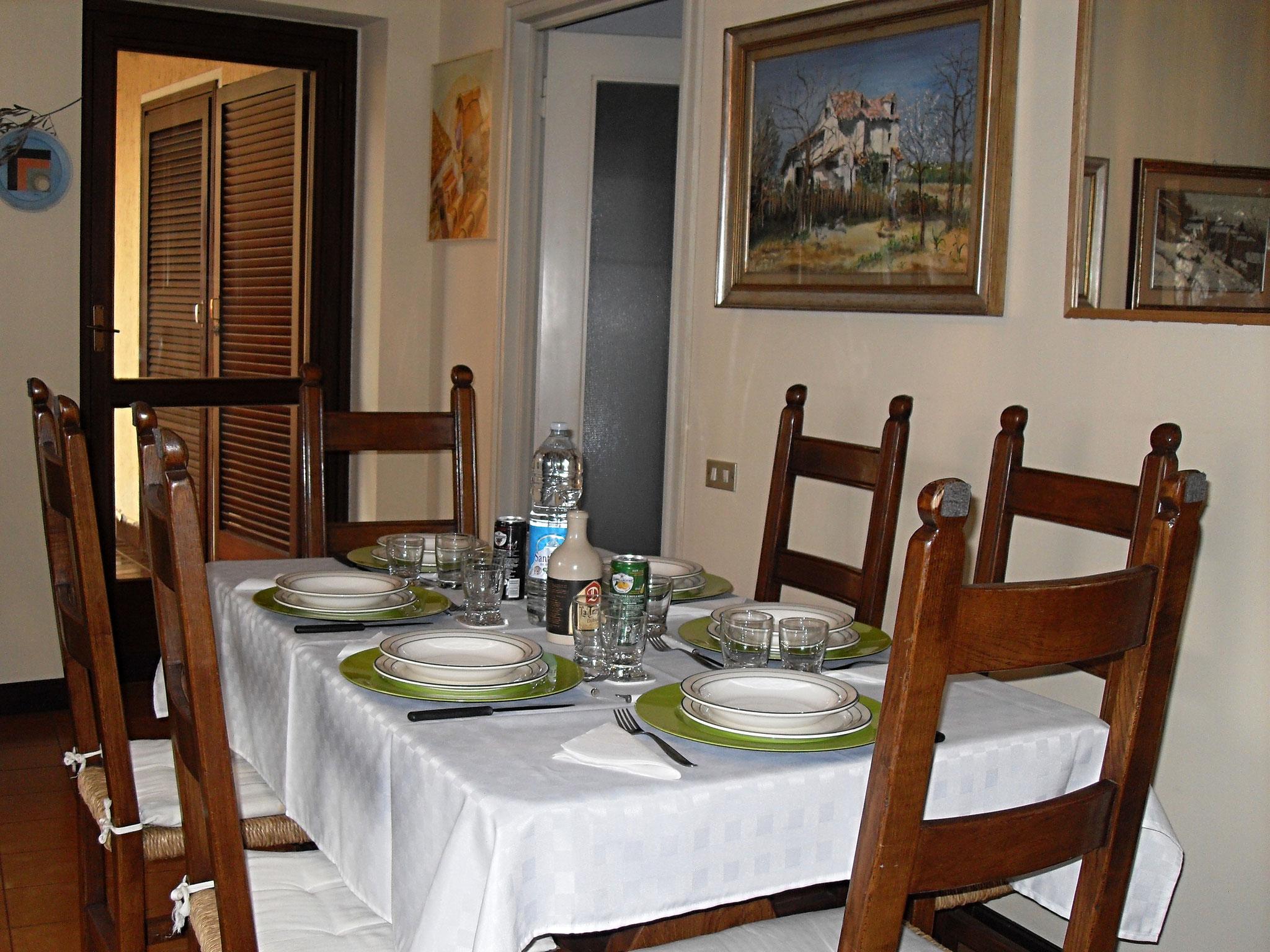 Tavolo da pranzo per 6 persone .  Sullo sfondo la portafinestra della terrazza e sulla dx la cucina