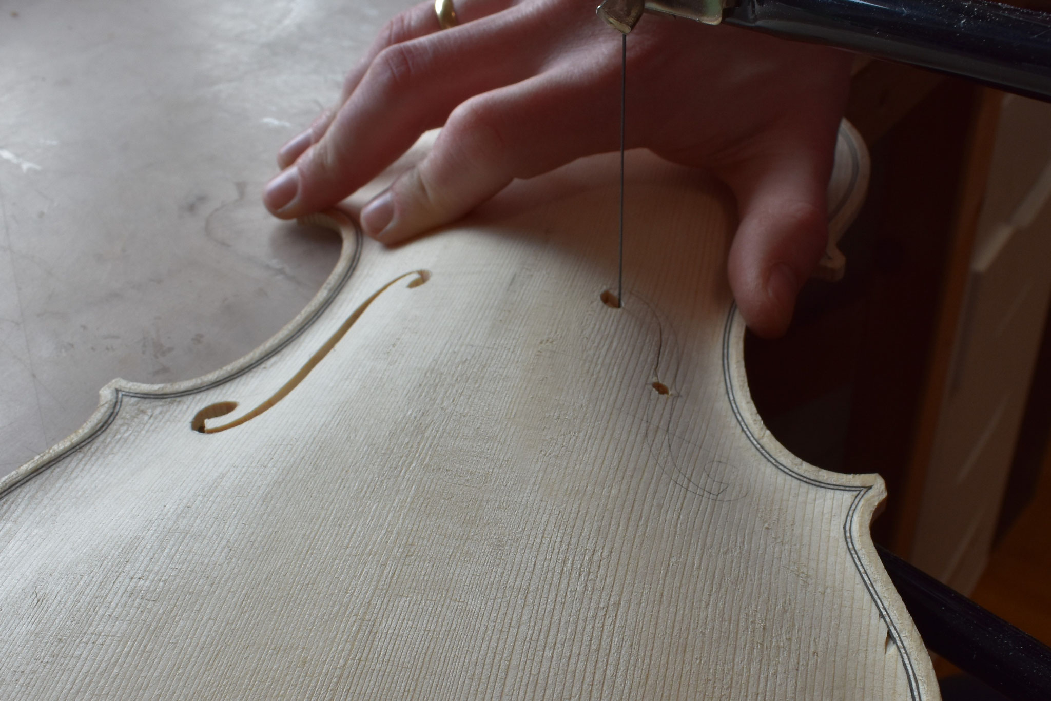 Nachdem die Decke grob ausgearbeitet wurde, werden die f-Löcher positioniert und mit einer Laubsäge ausgesägt.