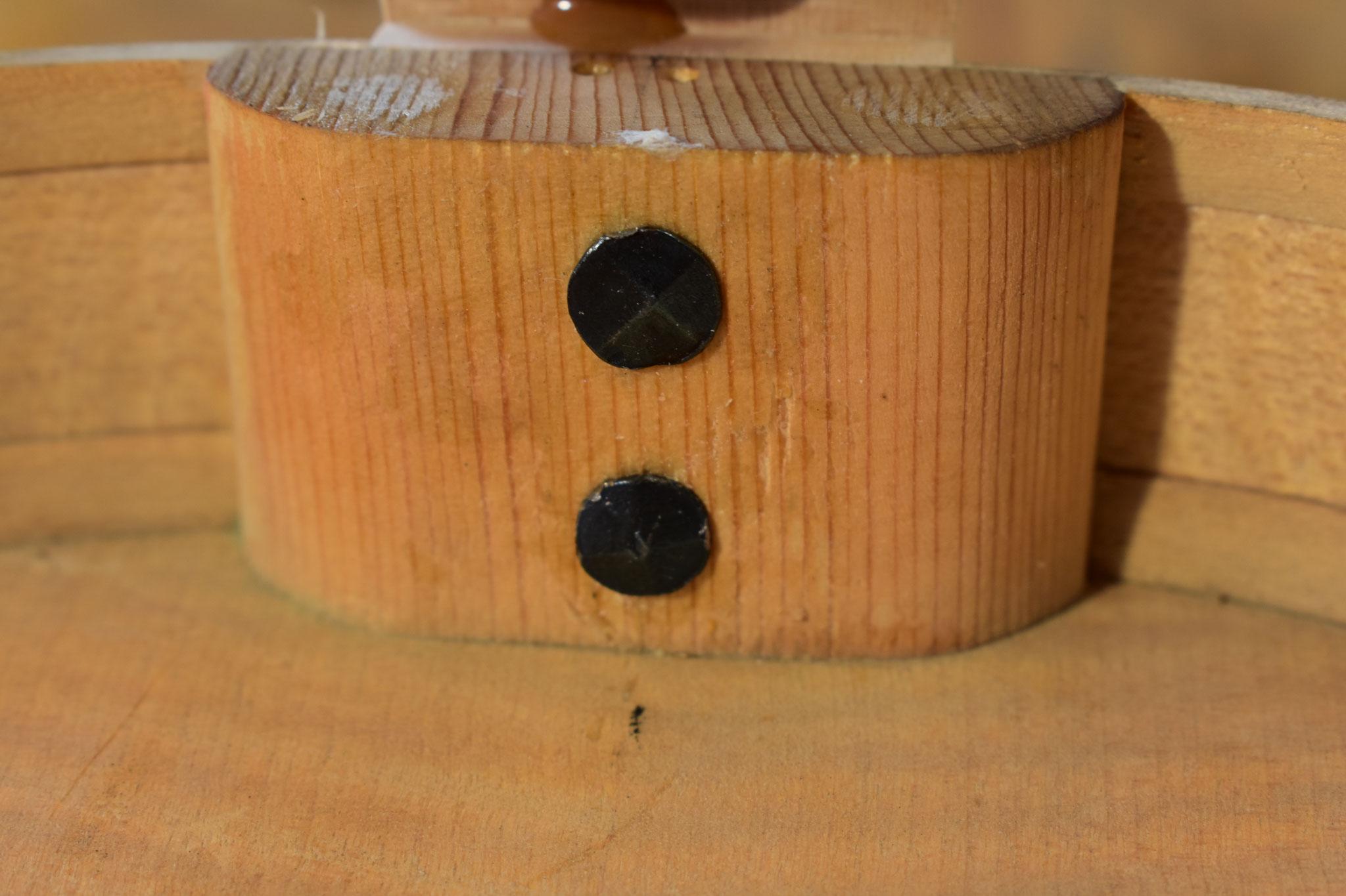 Zur Verstärkung der Verbindung werden Nägel durch den Oberklotz in den Hals getrieben.