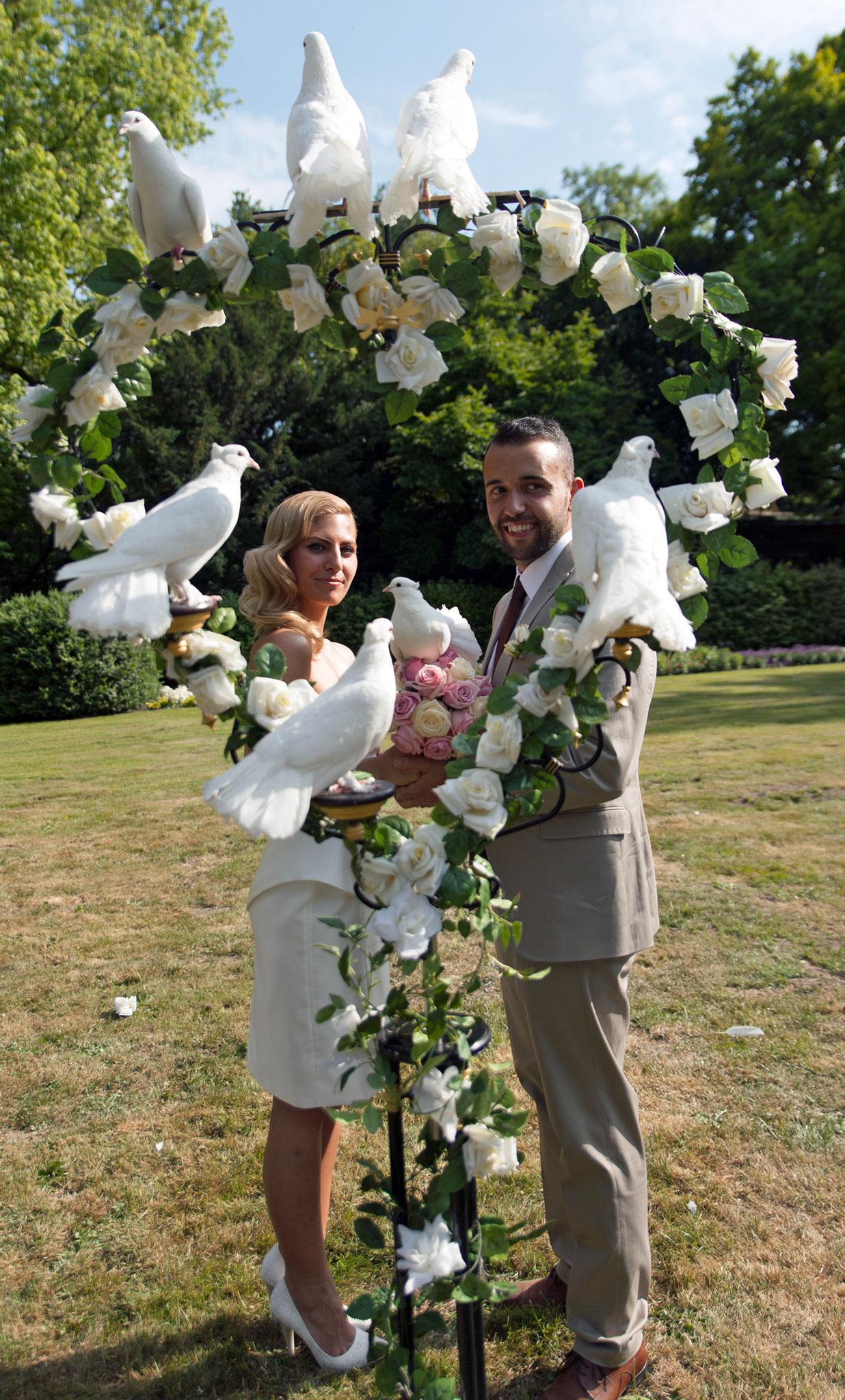 Brautpaar mit Rosenherz mit vielen weißen Tauben
