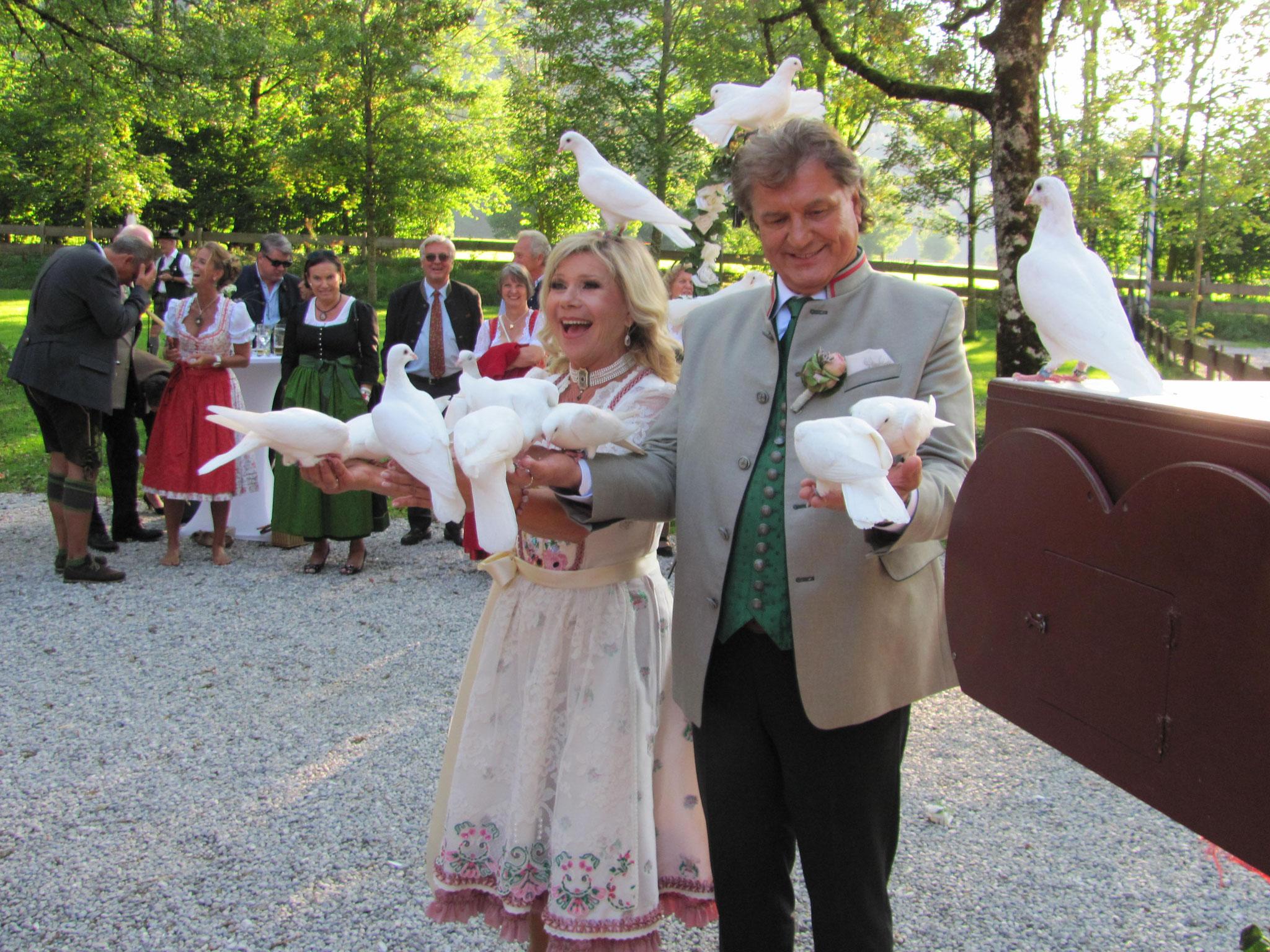 Brautpaar mit weißen Tauben auf der Hand