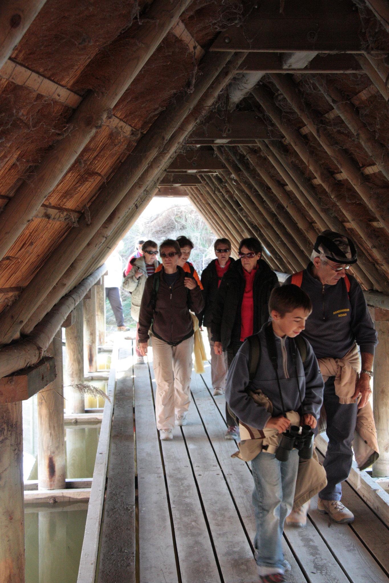 Visiteurs dans tunel couvert d'un toit en roseaux