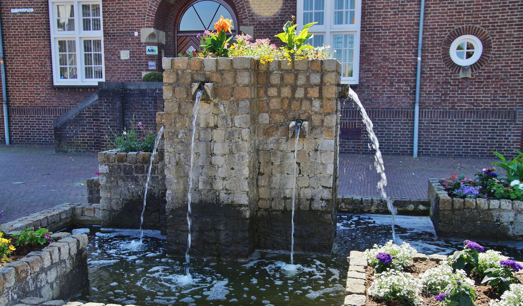 Ein Brunnen mit Blumen geschmückt