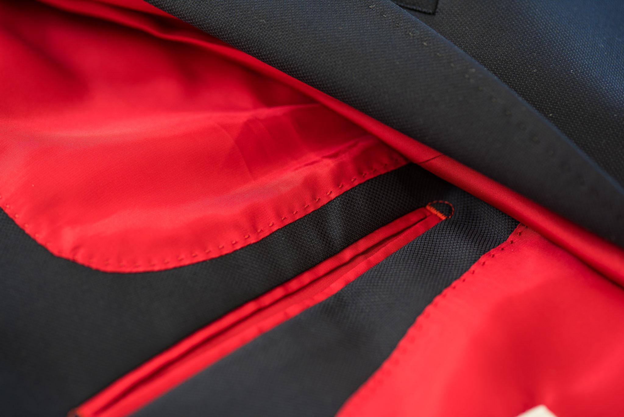 Rotes Kontrastfutter in strukturiertem dunkelblauem Herrensakko
