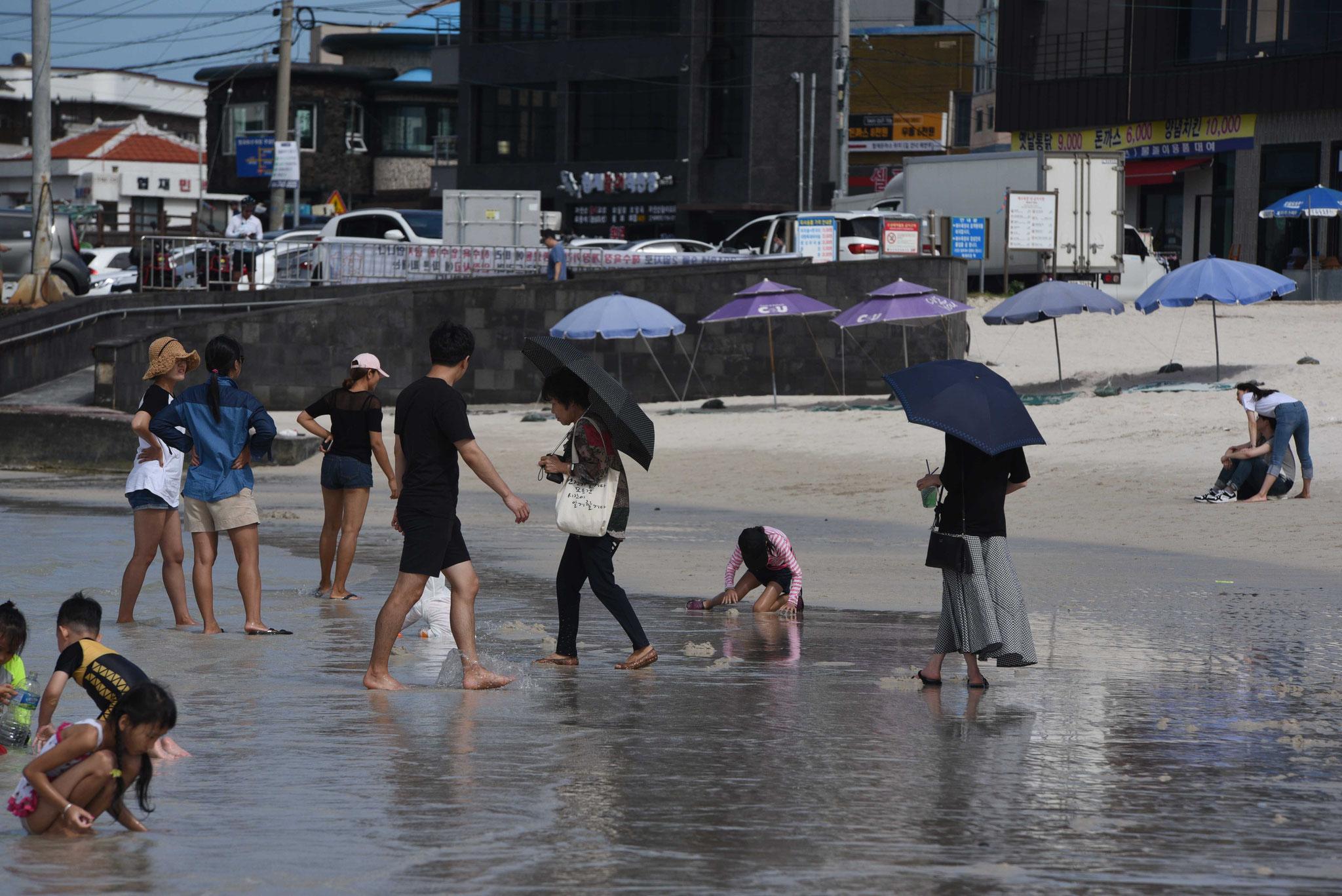 Kinder planschen noch ungeniert - Ältere schützen sichgegen die Sonne mit Schirmen