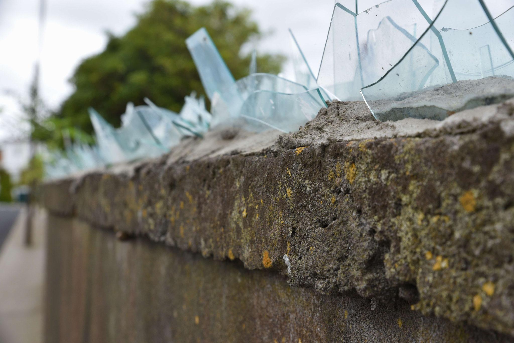 Mit Glasscherben gesicherte Mauer