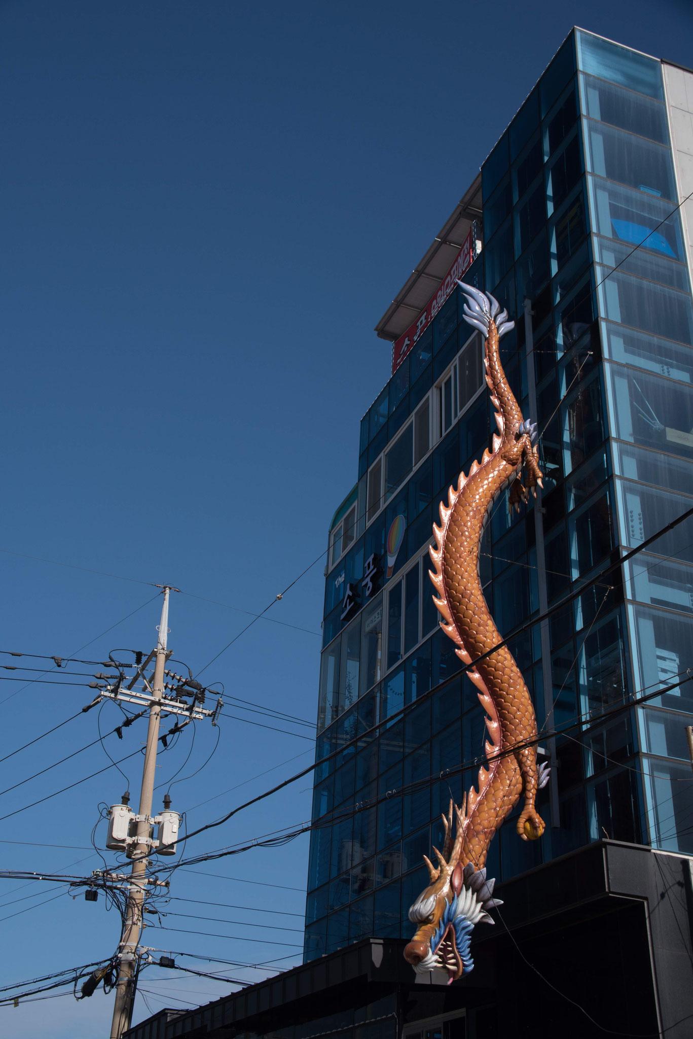Riesiger Drache an einer Bürohochhausfassade