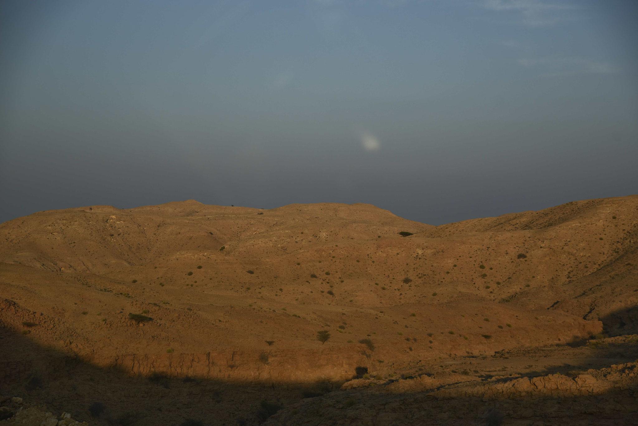 In der Dämmerung auf der Autobahn durch die Ausläufer des Hajar-Gebirges
