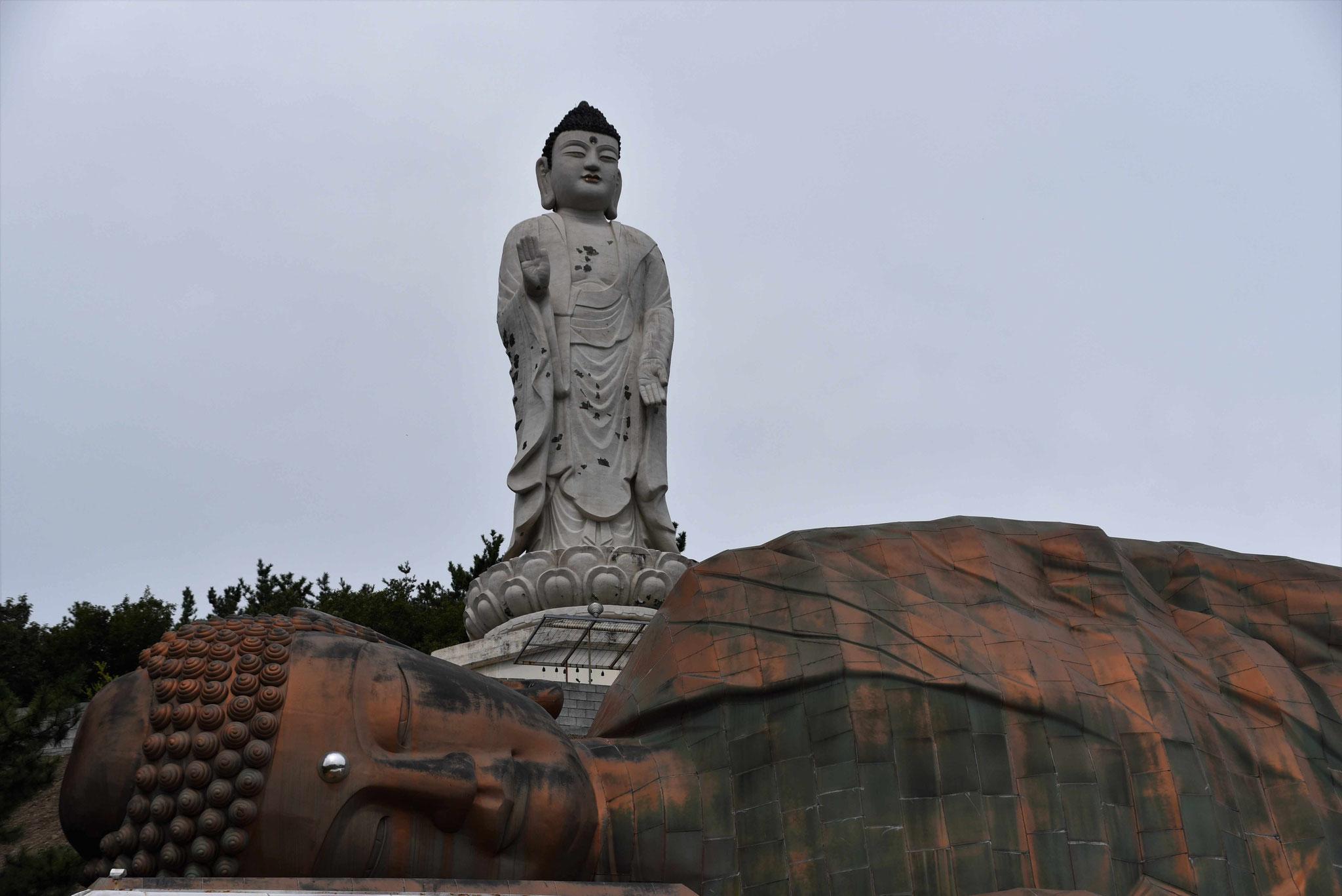 Kopf des liegenden Buddas vor dem großen stehenden Budda