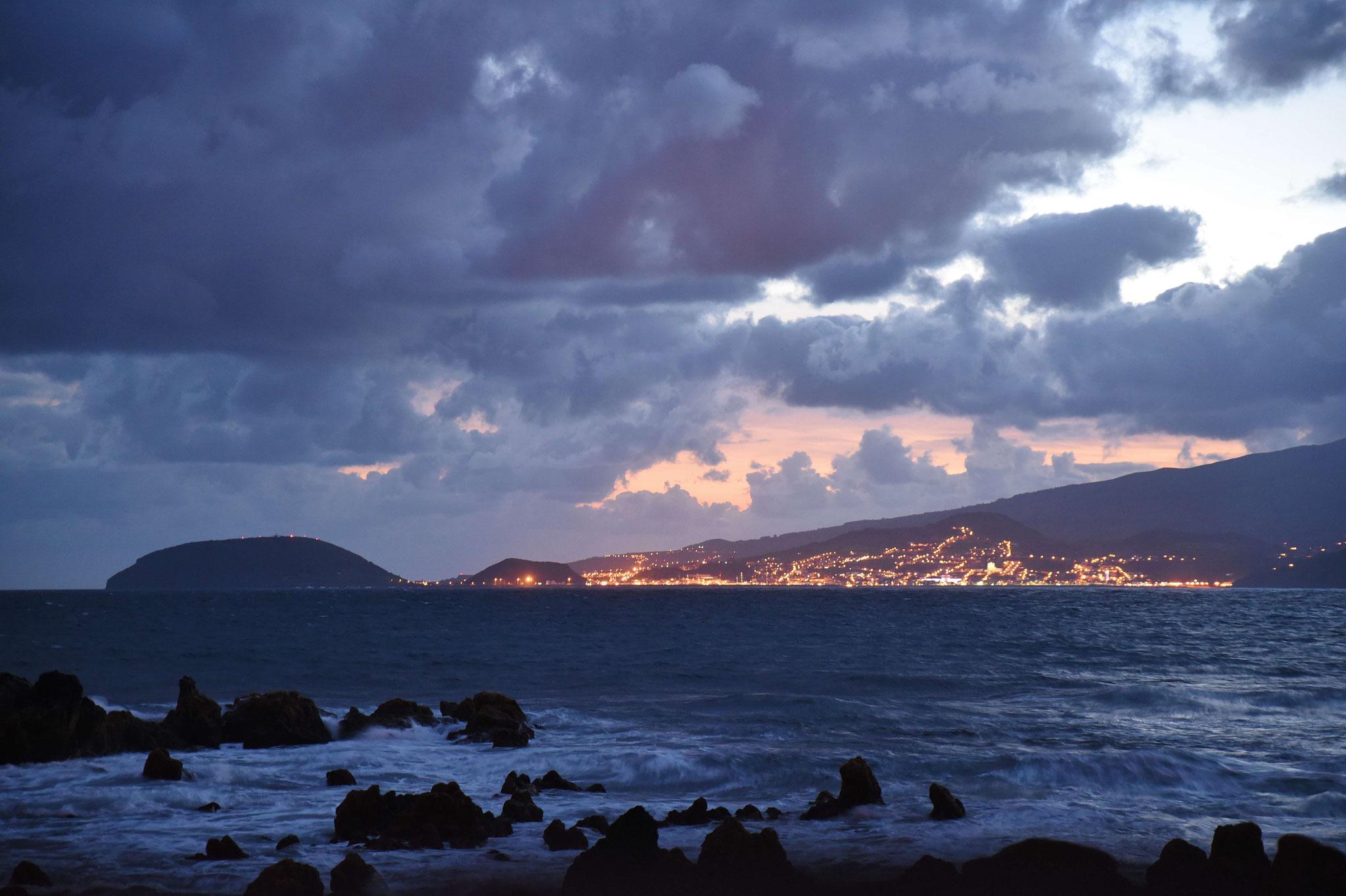 Abendspaziergang an der Küste, die Stadt Horta ist hell erleuchtet