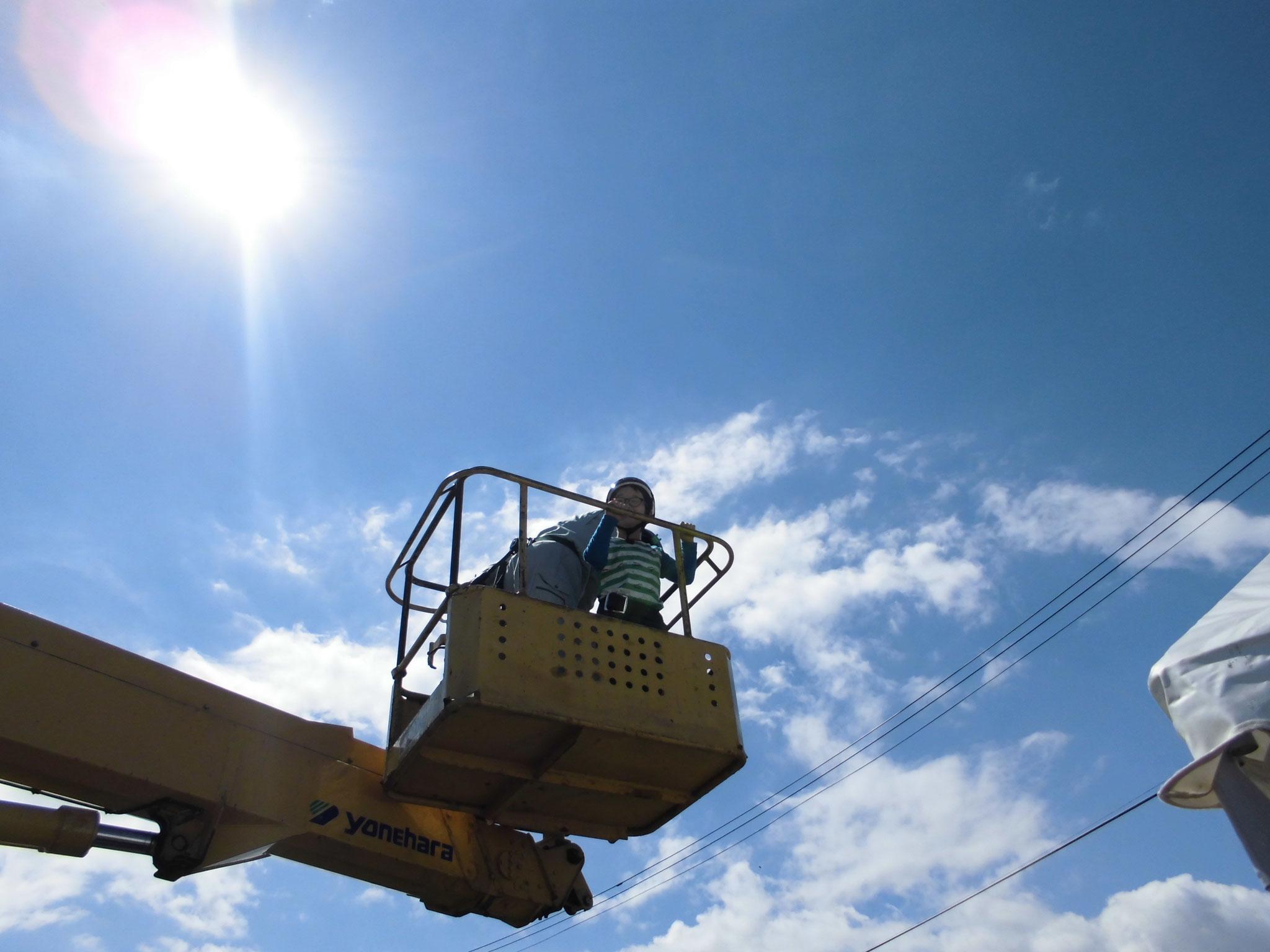 青空の中へ高所作業者のアームが伸びていきます