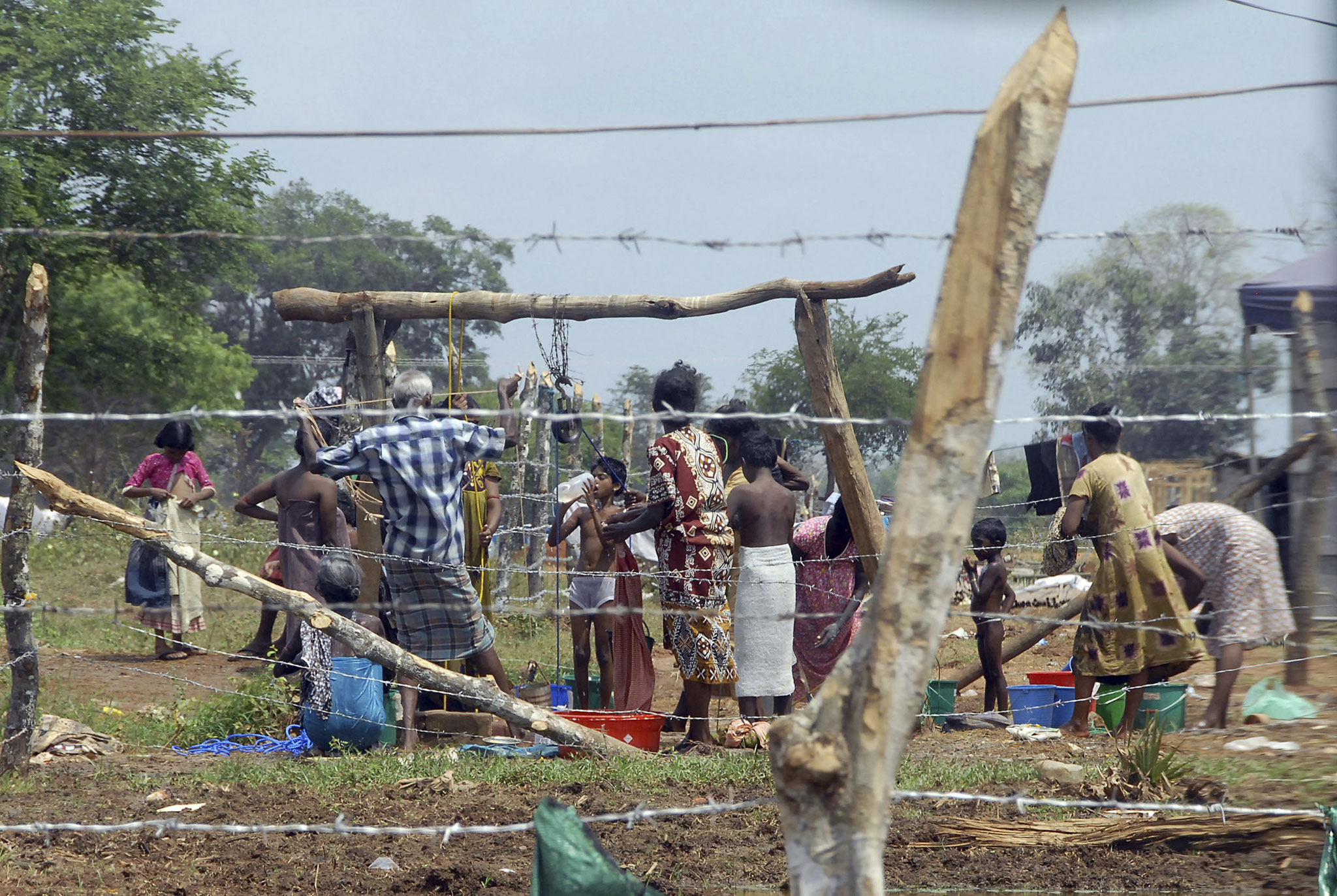 Desplazados internos civiles tamiles de Sri Lanka se reúnen alrededor de un pozo en un campamento de Manik Farm, Vavuniya, Sri Lanka (2009). AP Photo