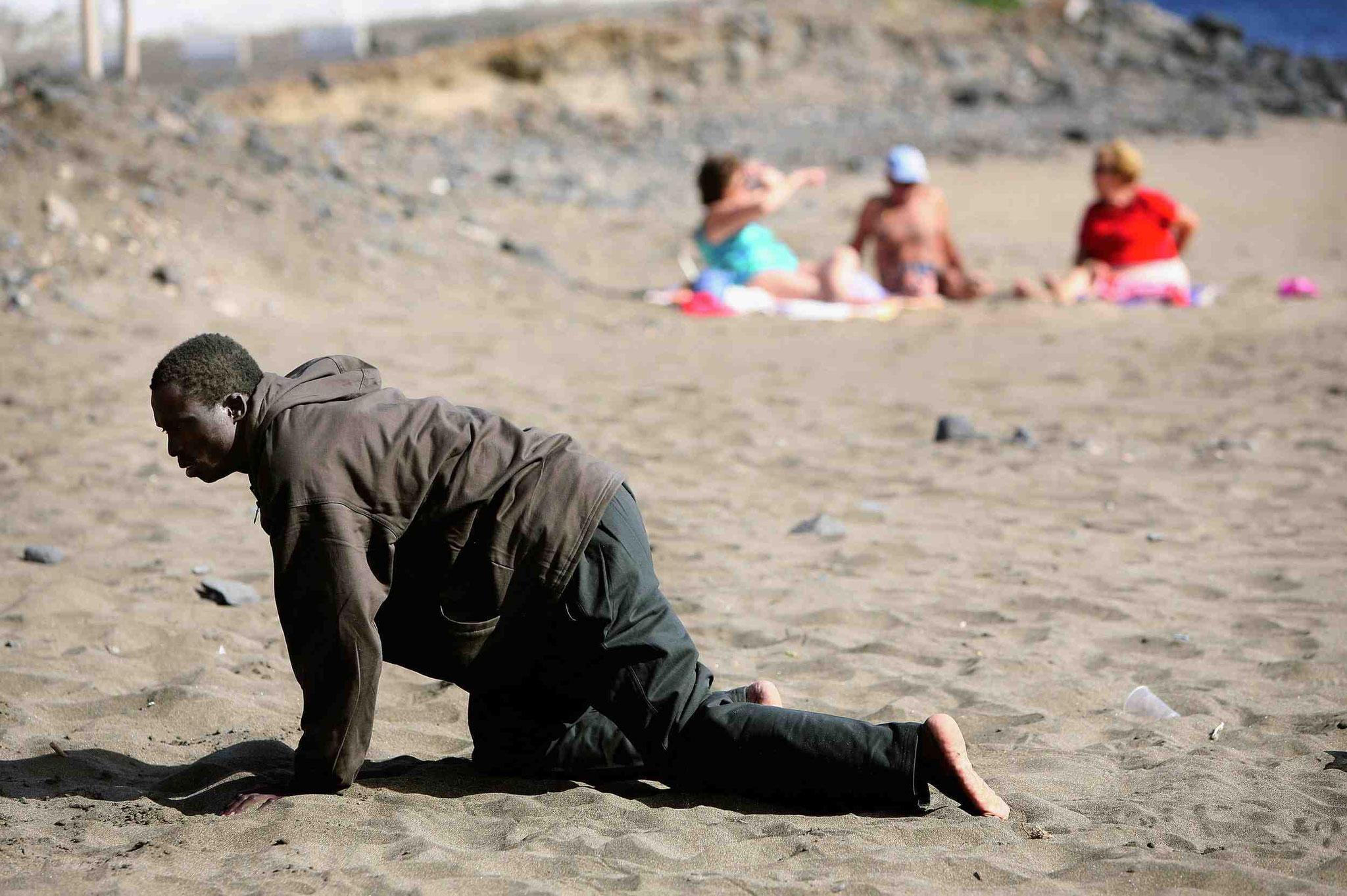 Un inmigrante se desplaza exhausto minutos después de desembarcar en la playa de Gran Tarajal, Fuerteventura (2005). Juan Medina/Reuters