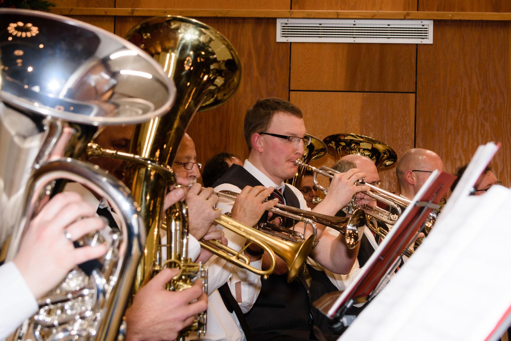 In den hinteren Reihen sind fast ausschließlich Blechblasinstrumente zu sehen.