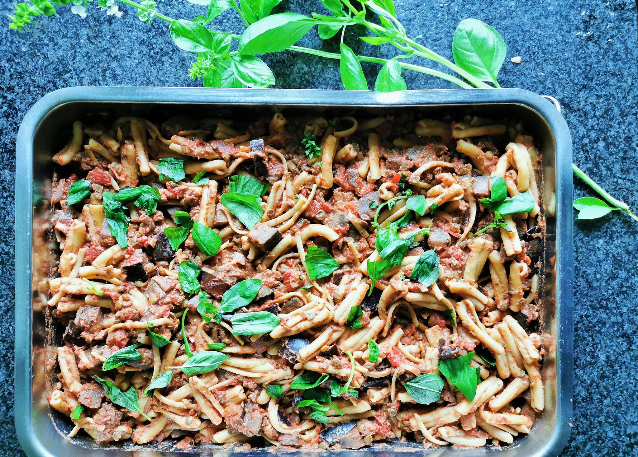 Nudeln mit der Sauce vermengen und in eine Auflaufform geben