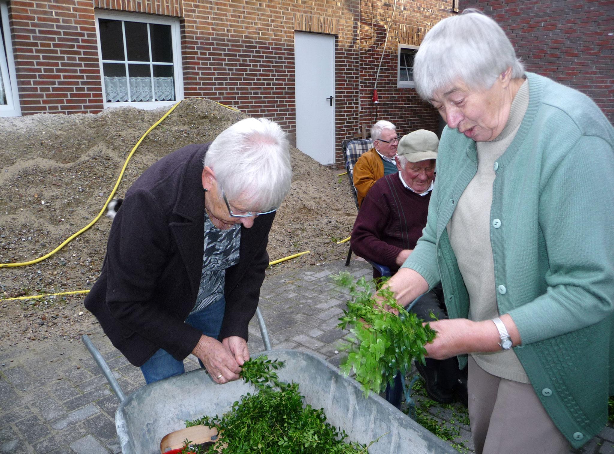 Gisela und Inge reichen ihm die Buchsbaumbündel
