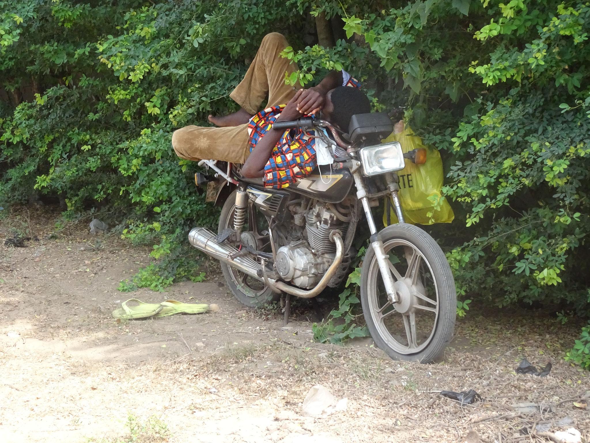 Ein alltägliches Bild. Ein Motorradtaxifahrer schläft auf seinem Motorrad.