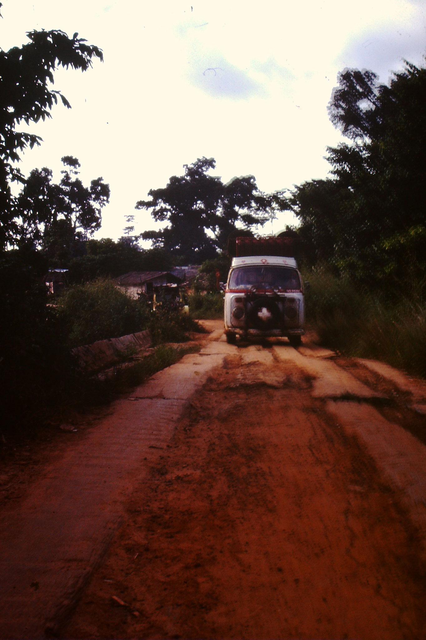 Eine etwas schlechtere Piste, mit Holz fahrbar gemacht. Der Bus steht kurz vor einer Brücke, der über das Bächlein Comoé führt.