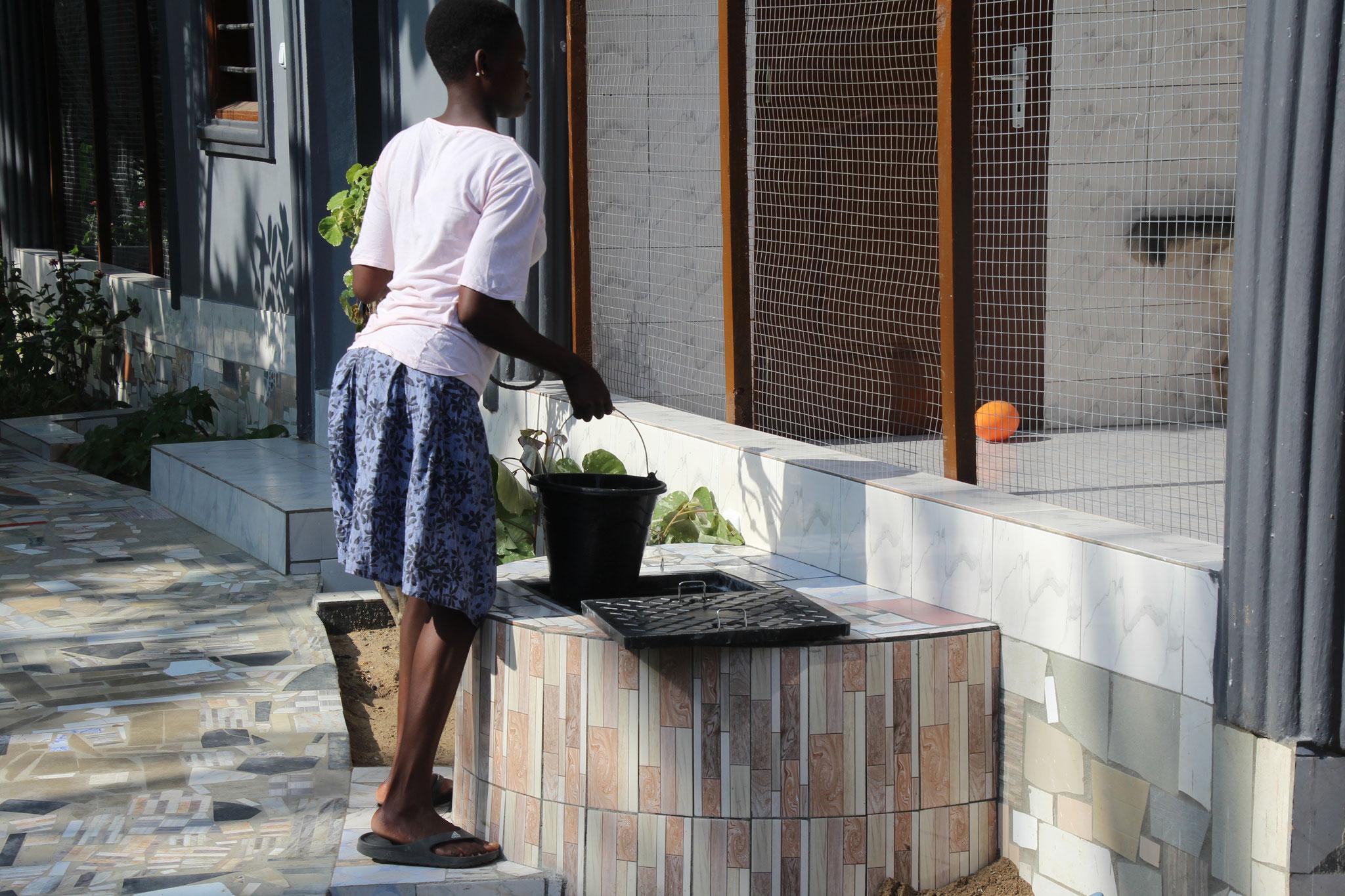 Afi holt Wasser am Brunnen.
