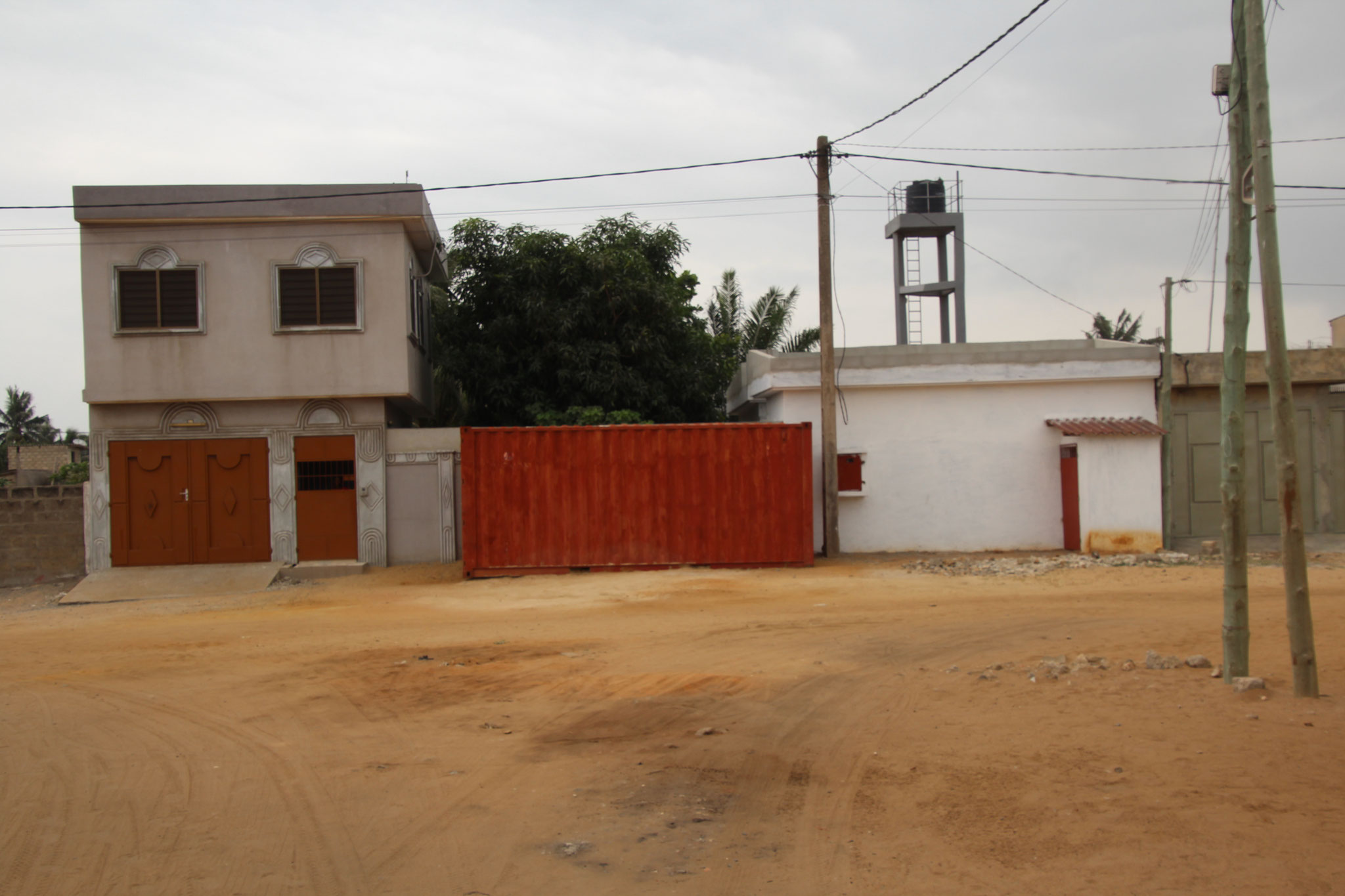 Links Garage und Appartement Rechts Afrikanische Küche mit Abfallensorgungsraum.