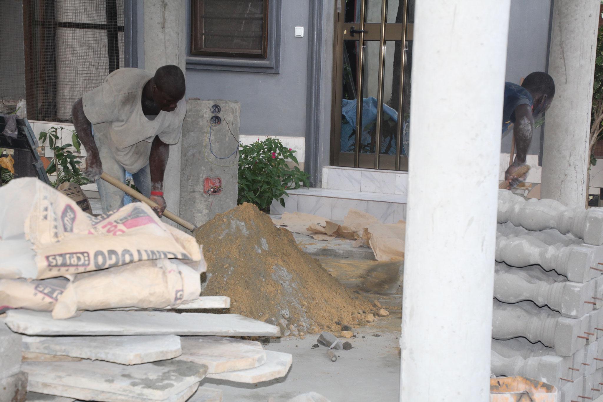 """Sand und Zement werden noch von Hand gemischt. Rechts im Bild die """"Schweinefüsse"""" Betonpföstchen für die Umrandung."""