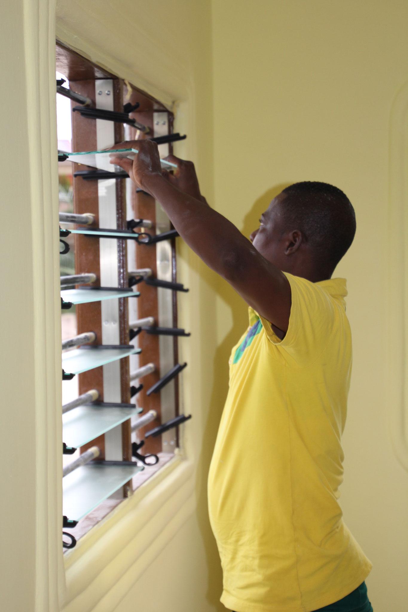 Ein Mitarbeiter von First-Alu passt die Fenster an.