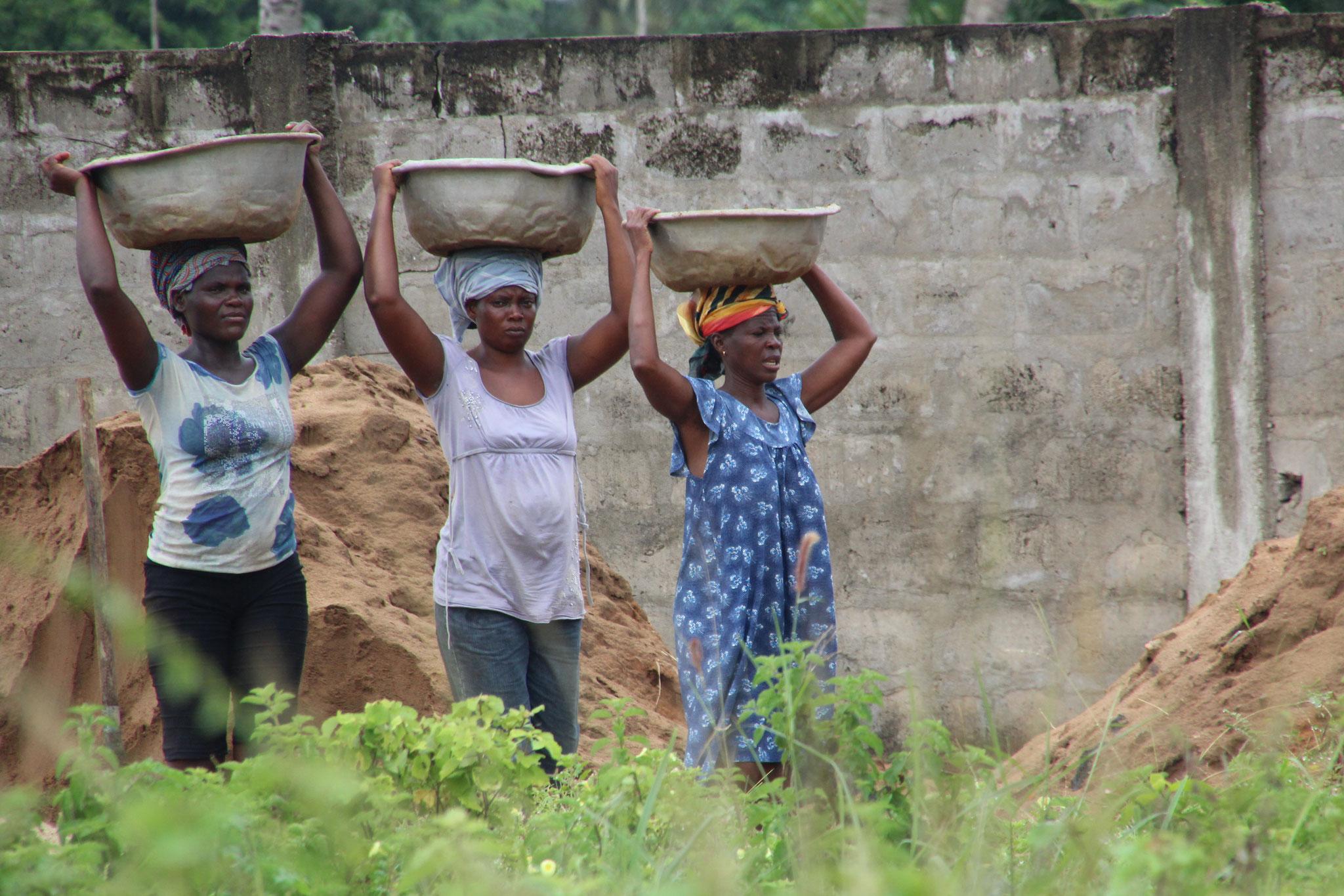 Frauen tragen Sand auf eine Baustelle