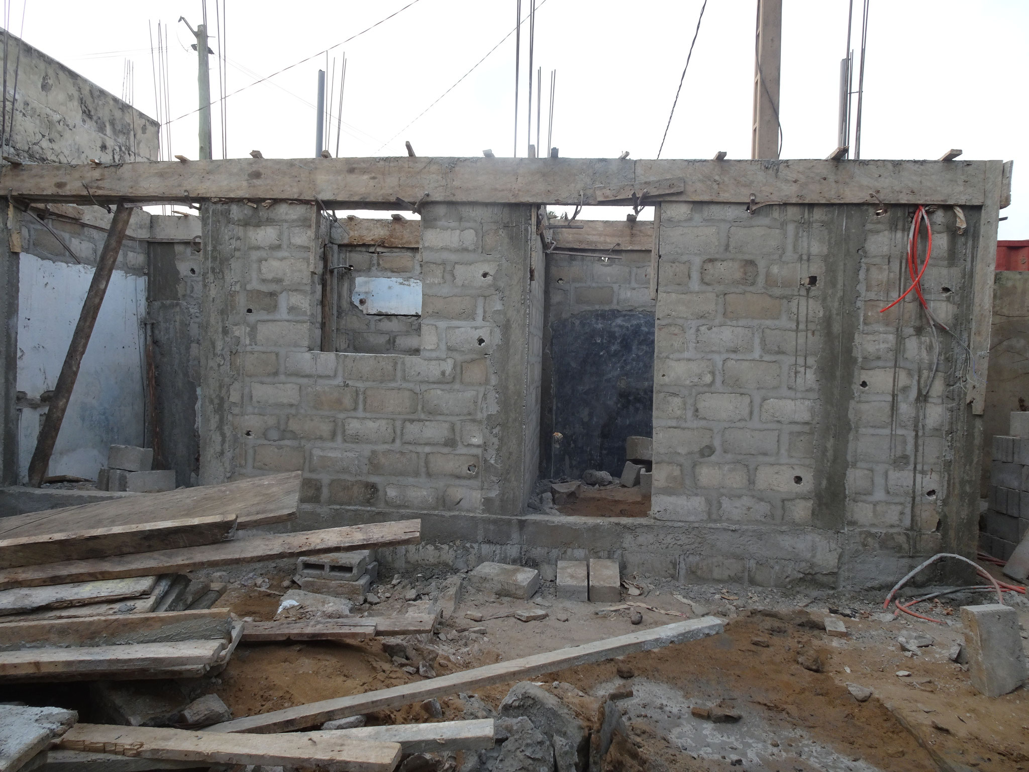 Oberhalb der Fenster und Türen ist Armierungseisen und Beton.