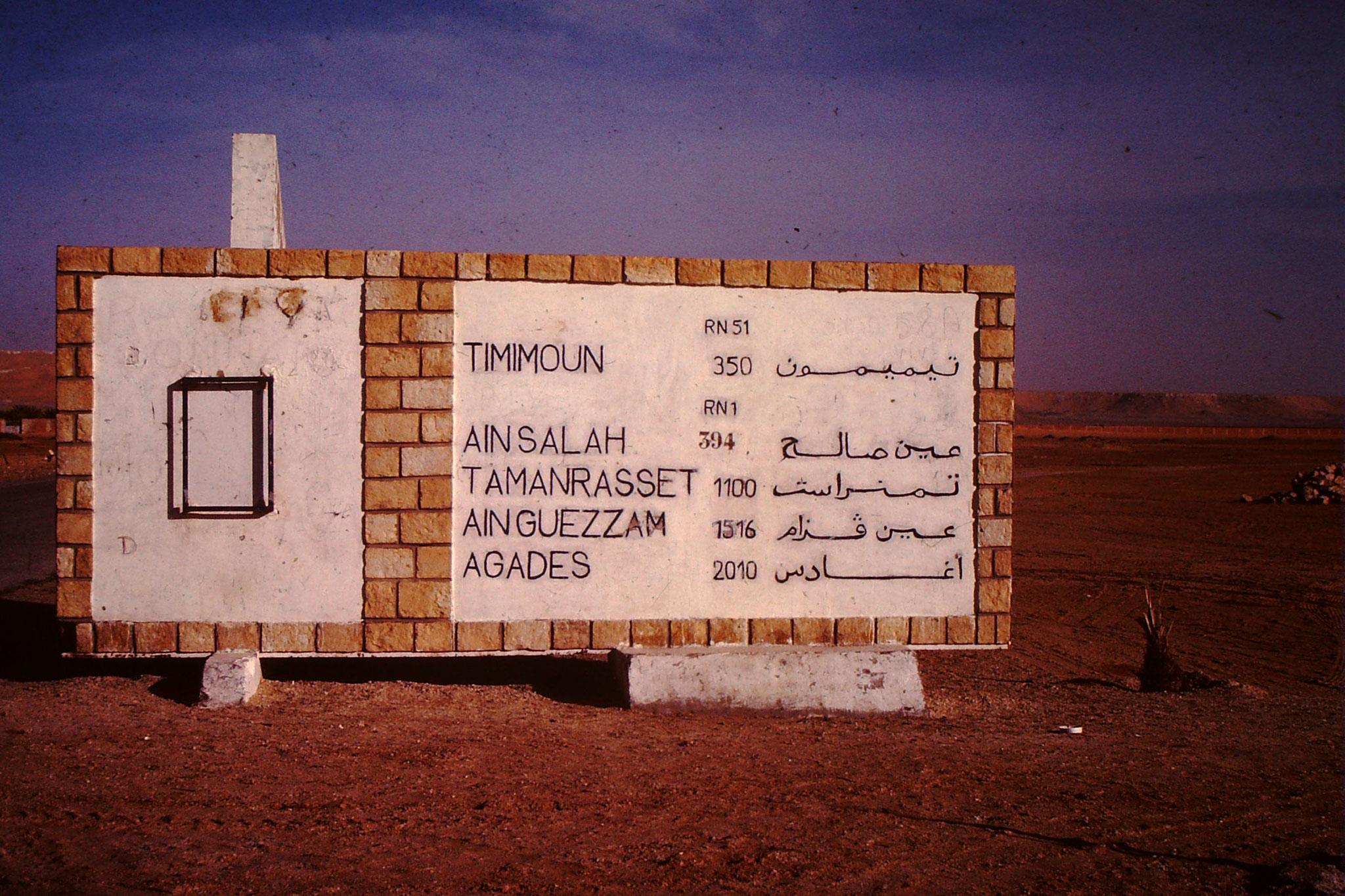 An diesem gemauerten Verkehrsschild wird einem bewusst, was für Distanzen man in der Wüste zurücklegen muss. Das Schild steht circa 6 km nach El Golea. Ain Guezzam ist die Grenze von Algerien.  Agadez ist die erste Stadt nach der Wüste in Niger.