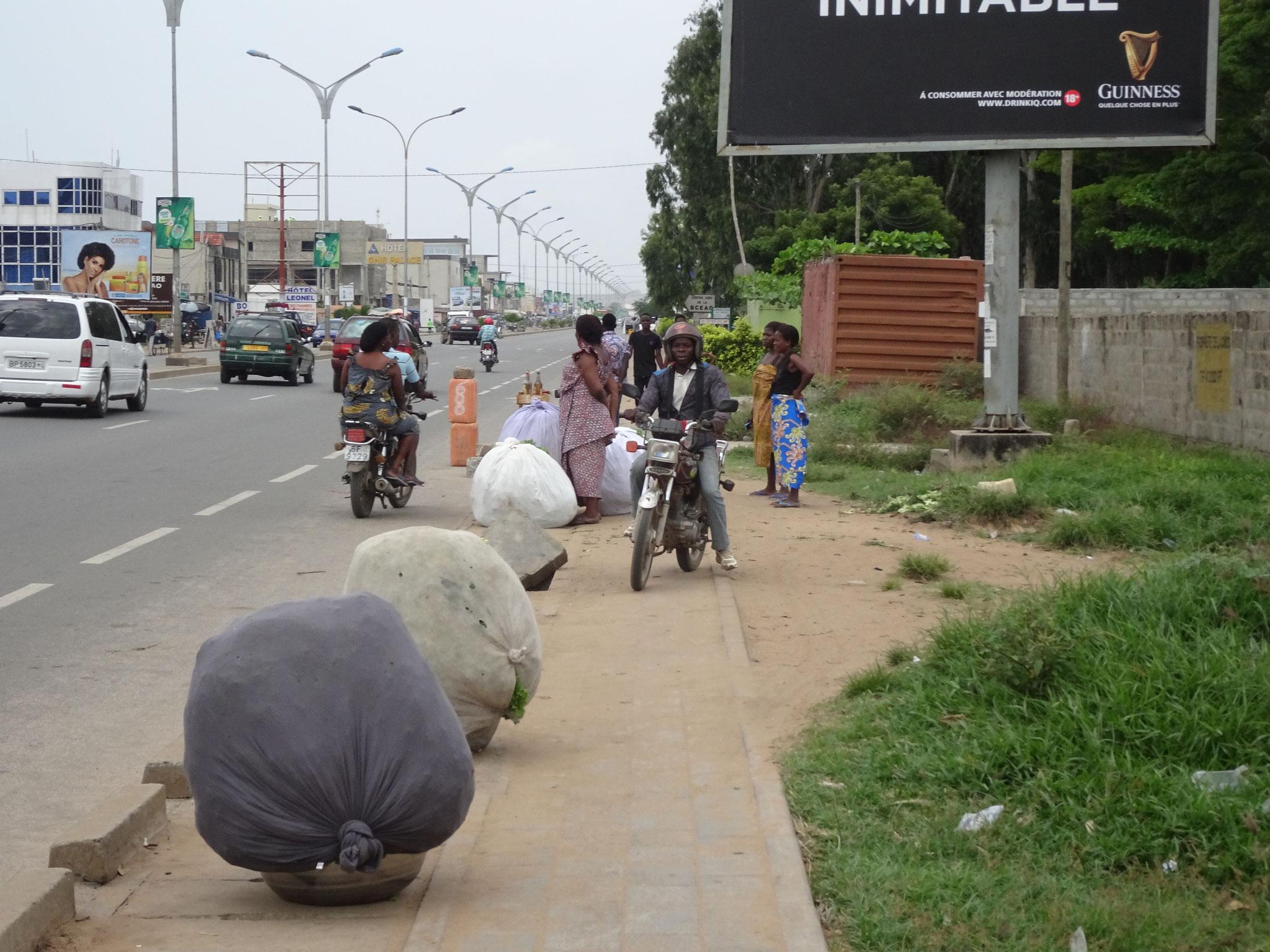 Das Frisch verpackte Gemüse wartet auf den Abtransport. Die Motorradfahrer zwängen sich aber auch noch durch.