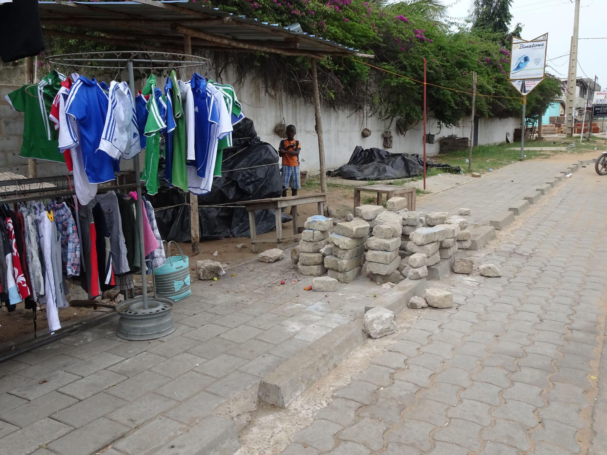 Die Marktfrau hat das Trottoir mit Backsteinen belegt. Sie wehrt sich so gegen rücksichtslose Motorradfahrer.