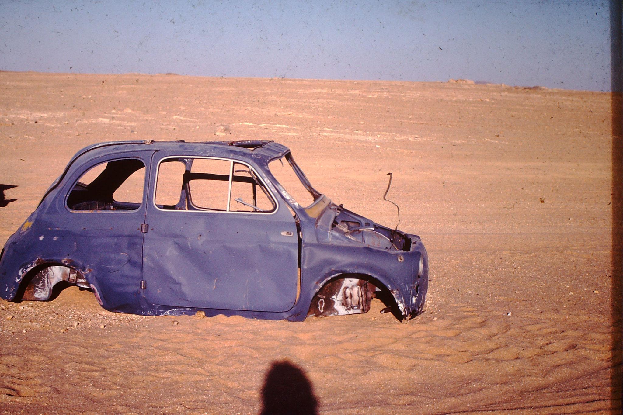 Dieser ausgeschlachtete Fiat 500 hat es nicht geschafft bis zur Grenzstadt Ain Guezzam. Ich habe mich insgesammt 3 mal  darauf verewigt. Beim 4. Mal fand ich in nicht mehr. Ob er einfach nur durch  Sandstürme zugedeckt war, oder er dem Strassenbau im